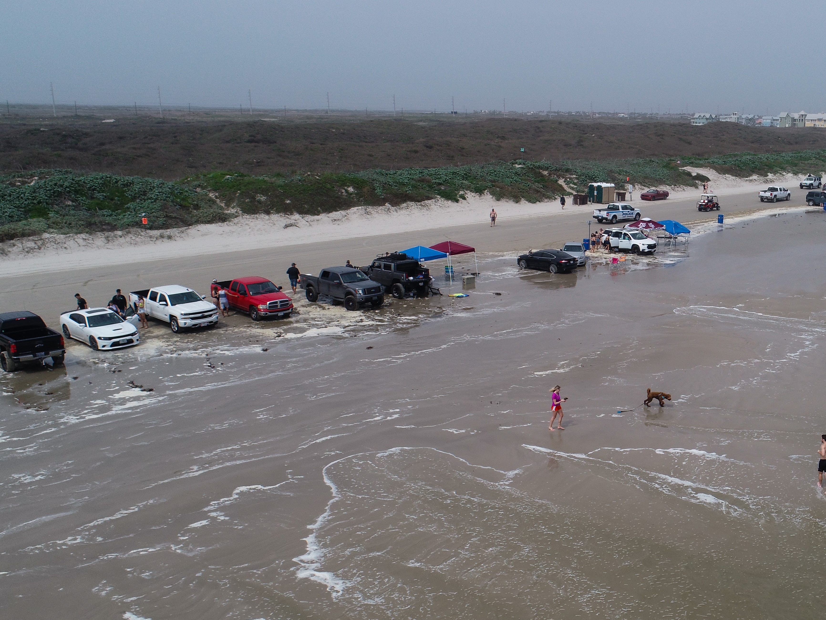 People walk in the surf on the  beach in Port Aransas during Spring Break 2019 on Wednesday, March, 13, 2019.