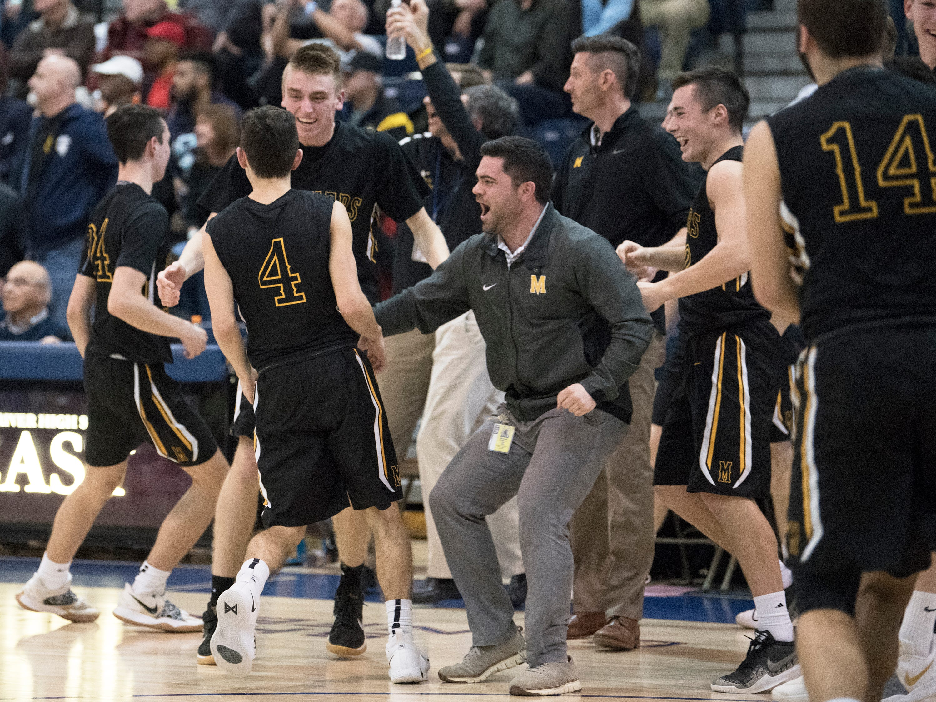 Members of the Moorestown High School boys basketball team celebrate with their coaches after Moorestown defeated Haddonfield 60-59 quarter in the boys basketball Tournament of Champions quarterfinal game played at Toms River North High School on Wednesday, March 13, 2019.