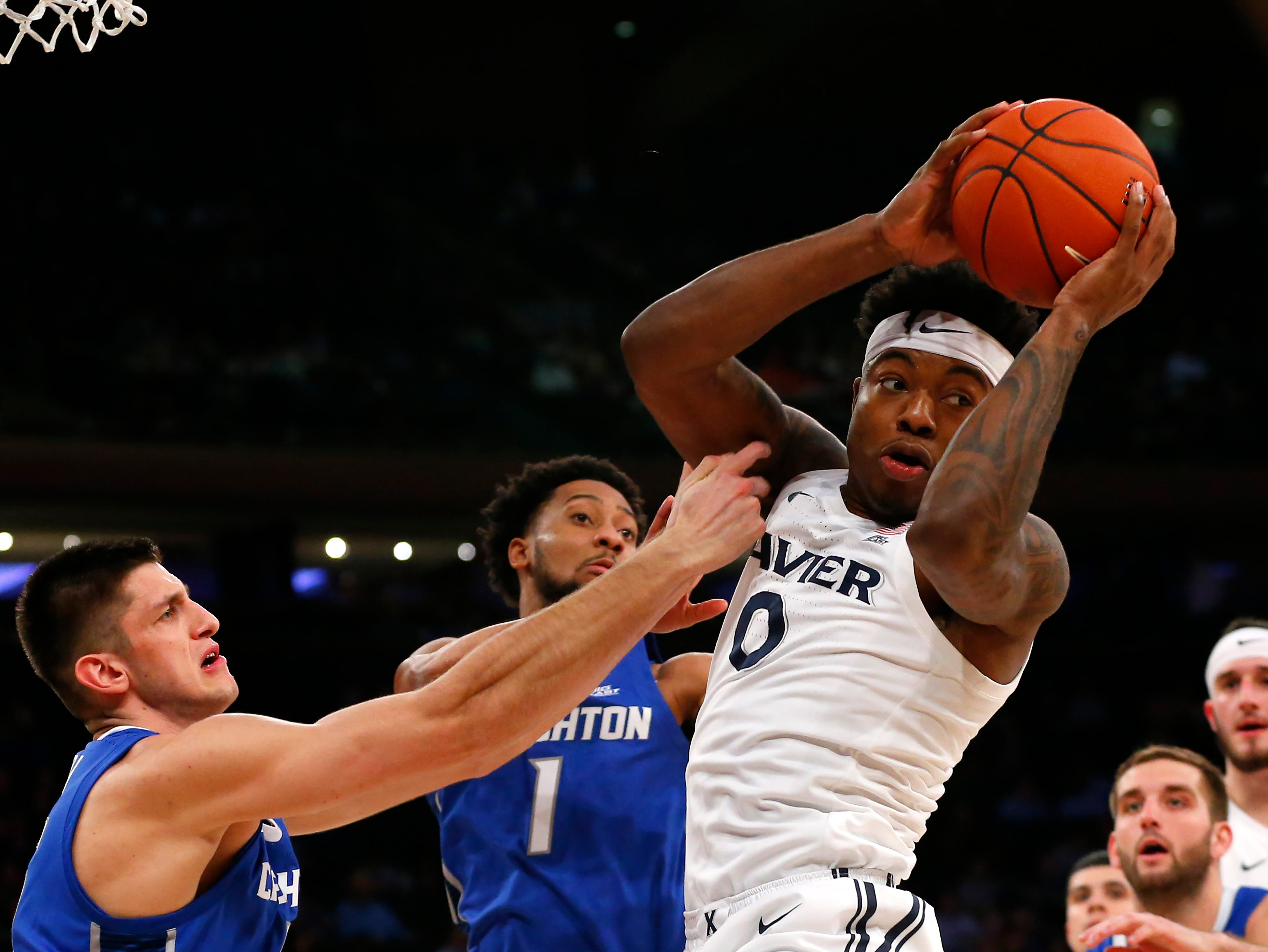 Creighton Bluejays forward Martin Krampelj (15) and guard Davion Mintz (1) defend against Xavier Musketeers forward Tyrique Jones (0) during the second half of a quarterfinal game of the Big East conference tournament at Madison Square Garden.