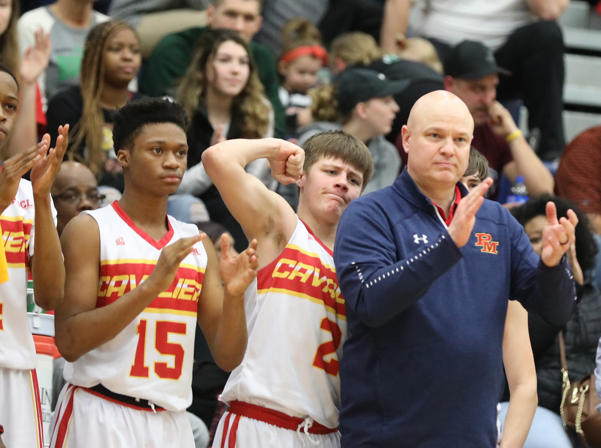 Purcell Marian head coach Scott Kerr and the Cavaliers bench react  during the Cavaliers' regional semifinal  win against Versailles Wednesday, March 13, 2019.