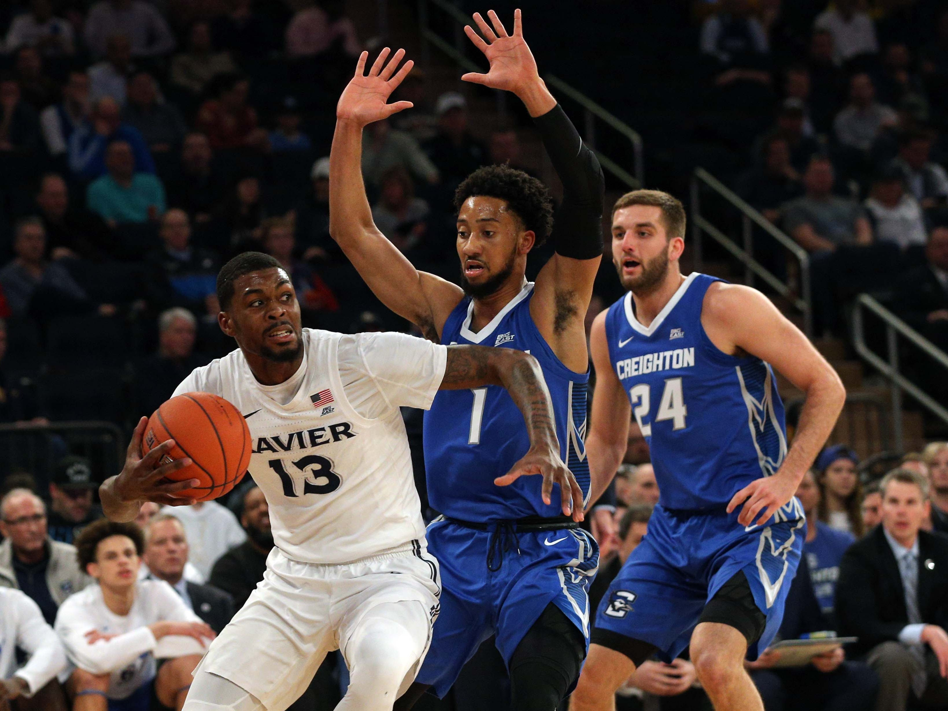 Xavier Musketeers forward Naji Marshall (13) controls the ball against Creighton Bluejays guards Davion Mintz (1) and Mitchell Ballock (24) during the first half of a quarterfinal game of the Big East conference tournament at Madison Square Garden.