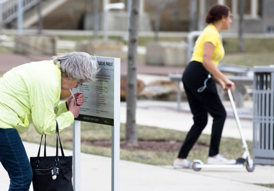 A pedestrian uses a sign to shield a cigarette from wind in order to light it at Smale Riverfront Park in Cincinnati on Thursday, March 14, 2019. The National Weather service issued a wind advisory and a tornado watch from 2 p.m. until 5 p.m. Thursday.