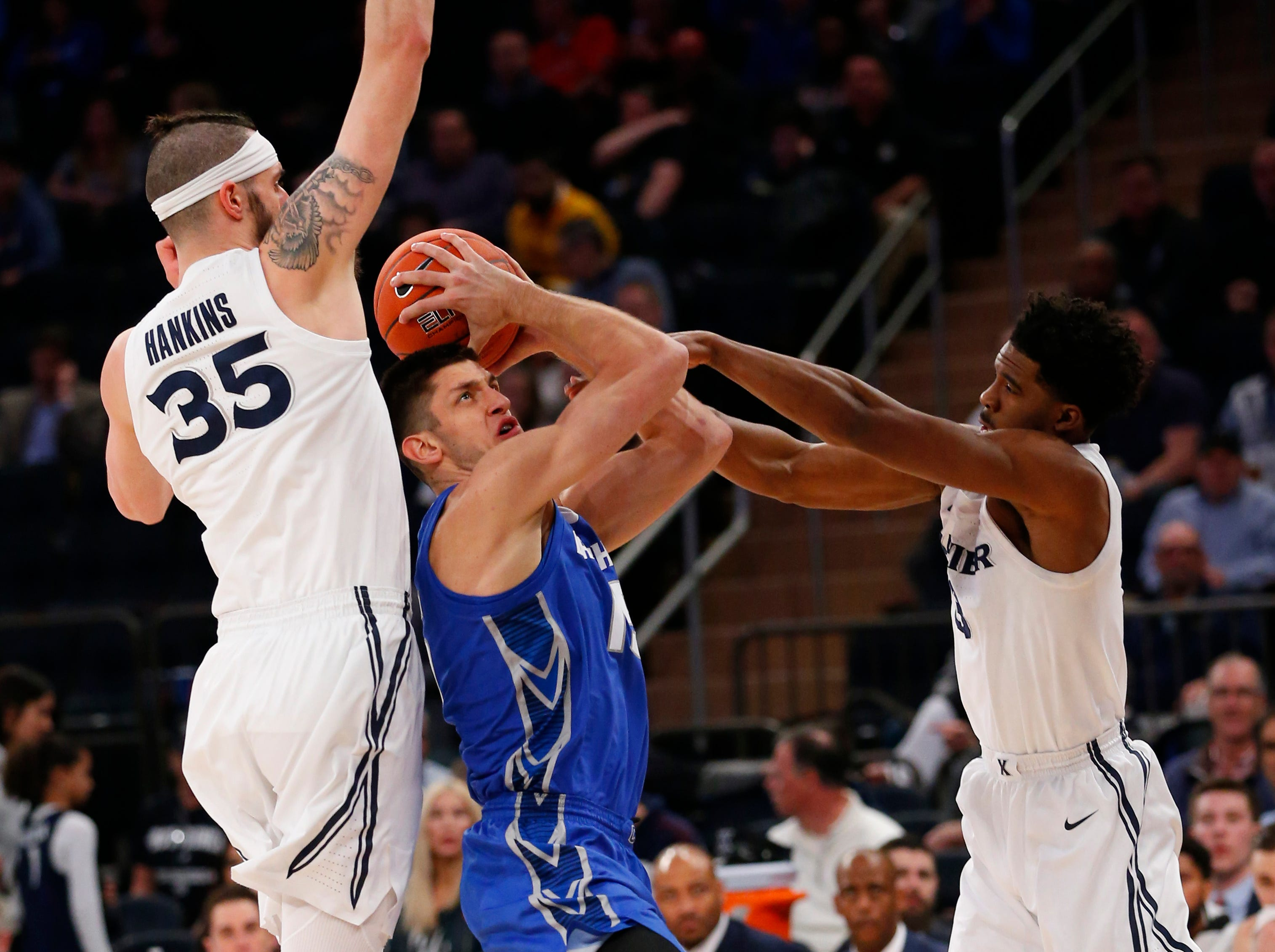 Creighton Bluejays forward Martin Krampelj (15) goes to the basket against Xavier Musketeers forward Zach Hankins (35) and guard Quentin Goodin (3) during the first half of a quarterfinal game of the Big East conference tournament at Madison Square Garden.