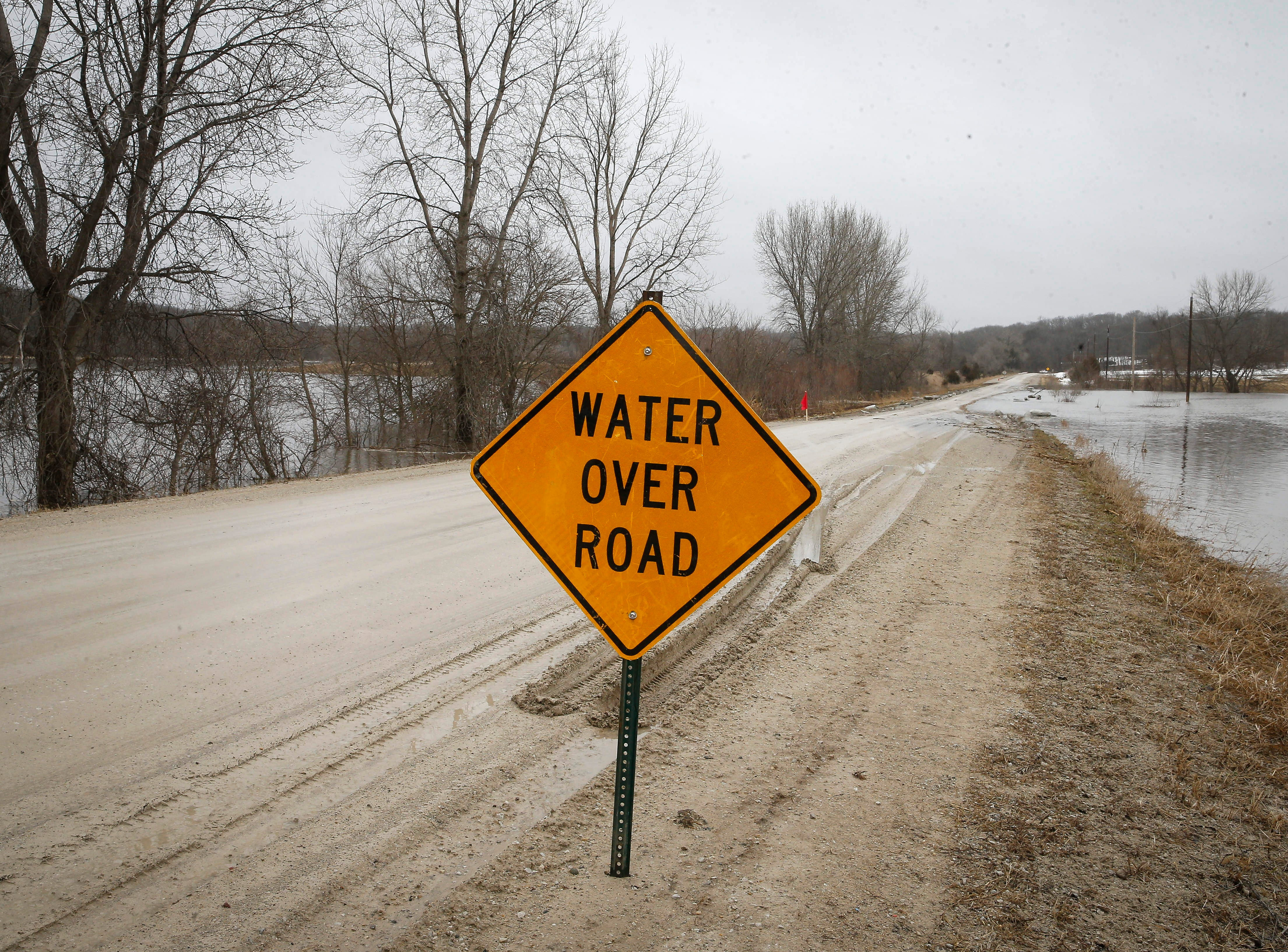 A sign warns of water over the road on H Avenue near Redfield after high water from the South Raccoon River flooded the road on Thursday, March 14, 2019.