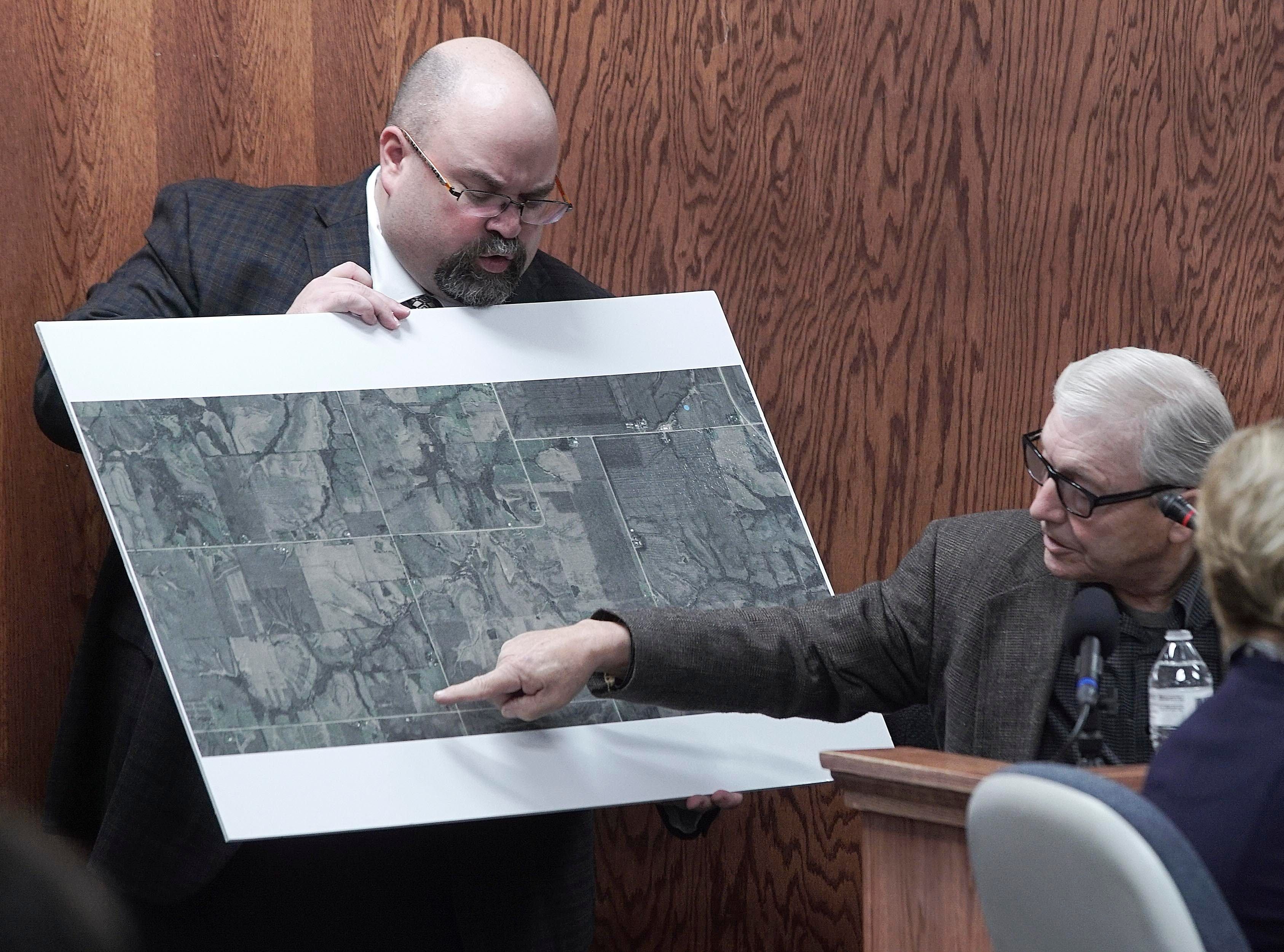 Bill Carter, 73, of Lacona, Iowa, points to his rural Marion County home on a map held by the county's prosecutor, Ed Bull, on Thursday, March 14, 2019, during the murder trial of his son, Jason Carter, at the Pottawattamie County Courthouse in Council Bluffs. Jason Carter is accused of fatally shooting his mother, Shirley Carter, in 2015 at the farm where she and Bill Carter lived.