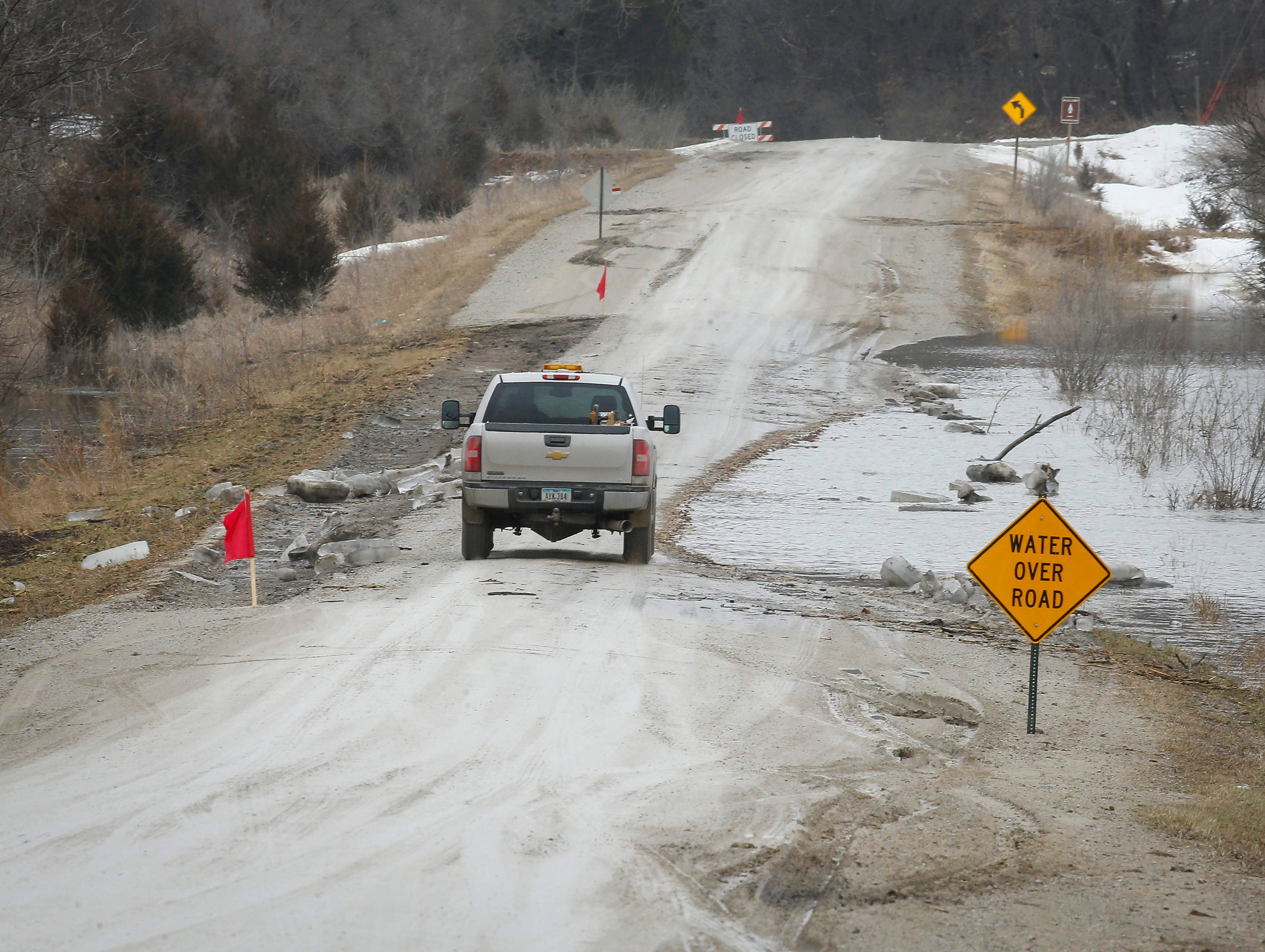 A driver navigates a truck across a small portion of road on H Avenue near Redfield in Dallas County after high water from the South Raccoon River flooded the road on Thursday, March 14, 2019.