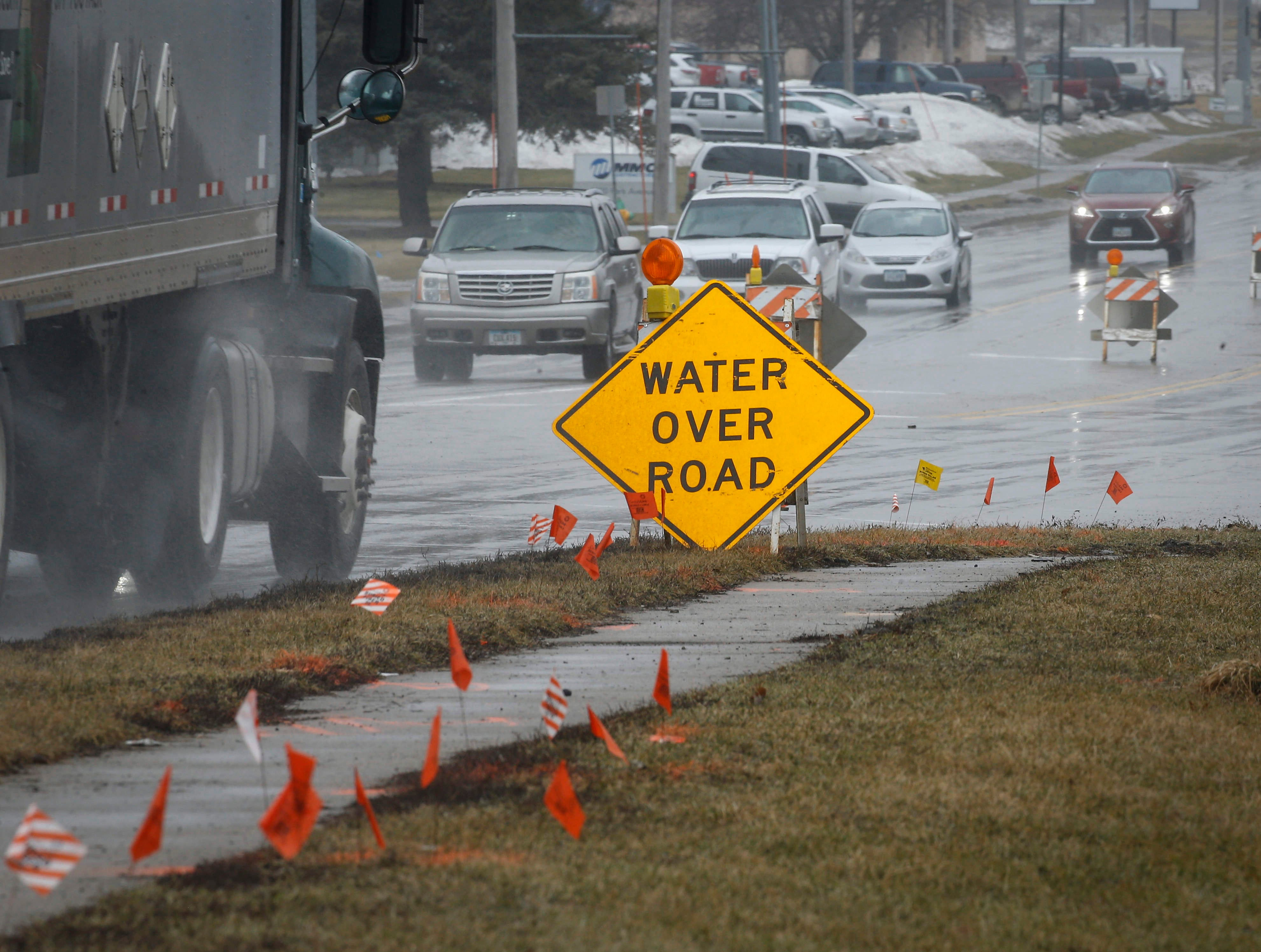 Signs warn motorists of high water on Park Ave. in West Des Moines on Thursday, March 14, 2019.