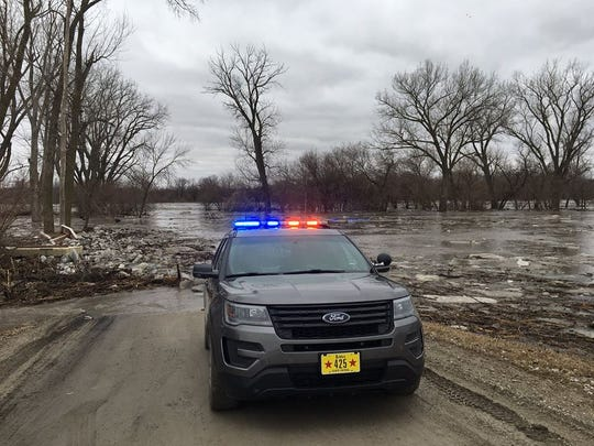 An Iowa State Patrol vehicle parked near icy floodwaters in Mills County near Council Bluffs on Wednesday, March 14, 2019.