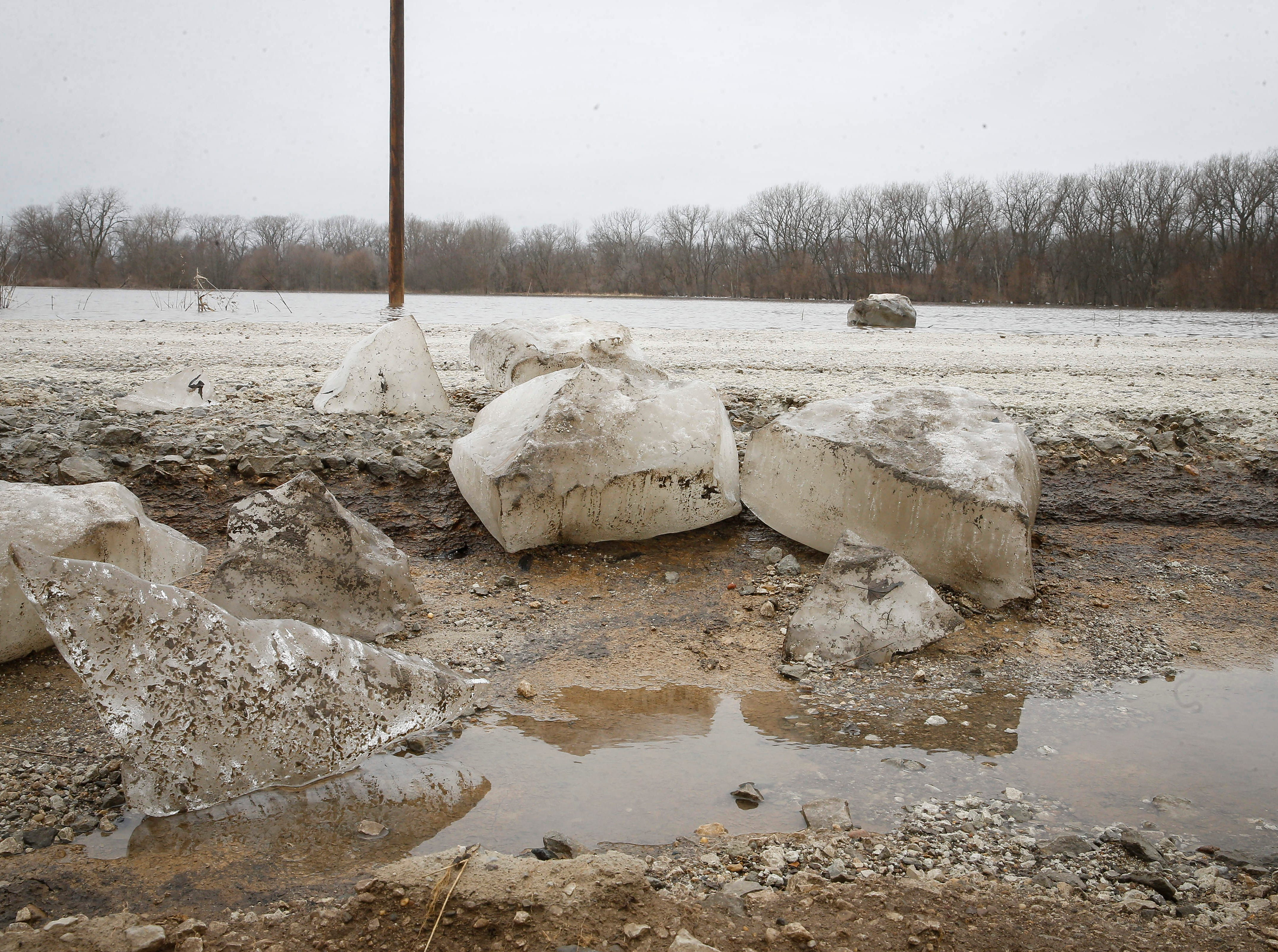 Large chunks of ice rest along a washed out portion of H Avenue near Redfield in Dallas County after water from the South Raccoon River flooded the road on Thursday, March 14, 2019.