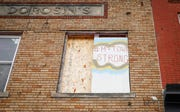 "An ""M-Town Strong"" sign on a building reflects the spirit of Marshalltown residents as the rebuilding effort continues nearly eight months after an EF-3 tornado ripped across downtown, toppling foundations and causing millions in property damage."