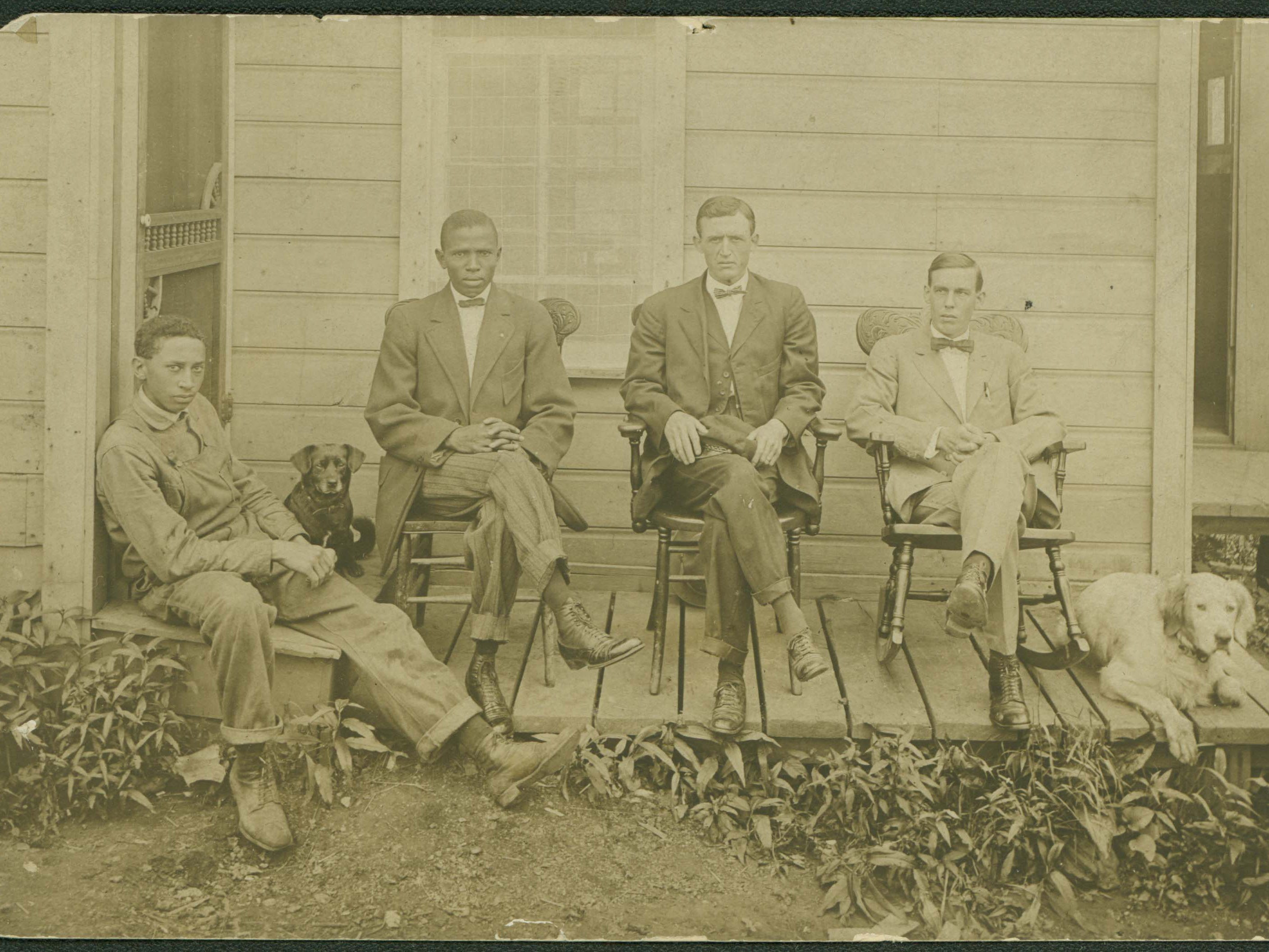 Buxton doctors Carter, Powell, and Gray seated on the porch of their practice with associate James Warren at far left.