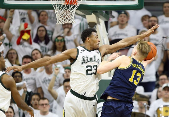 Mar 9, 2019; East Lansing, MI, USA; Michigan State Spartans forward Xavier Tillman (23) blocks the shot of Michigan Wolverines forward Ignas Brazdeikis (13) during the second half of a game at the Breslin Center.
