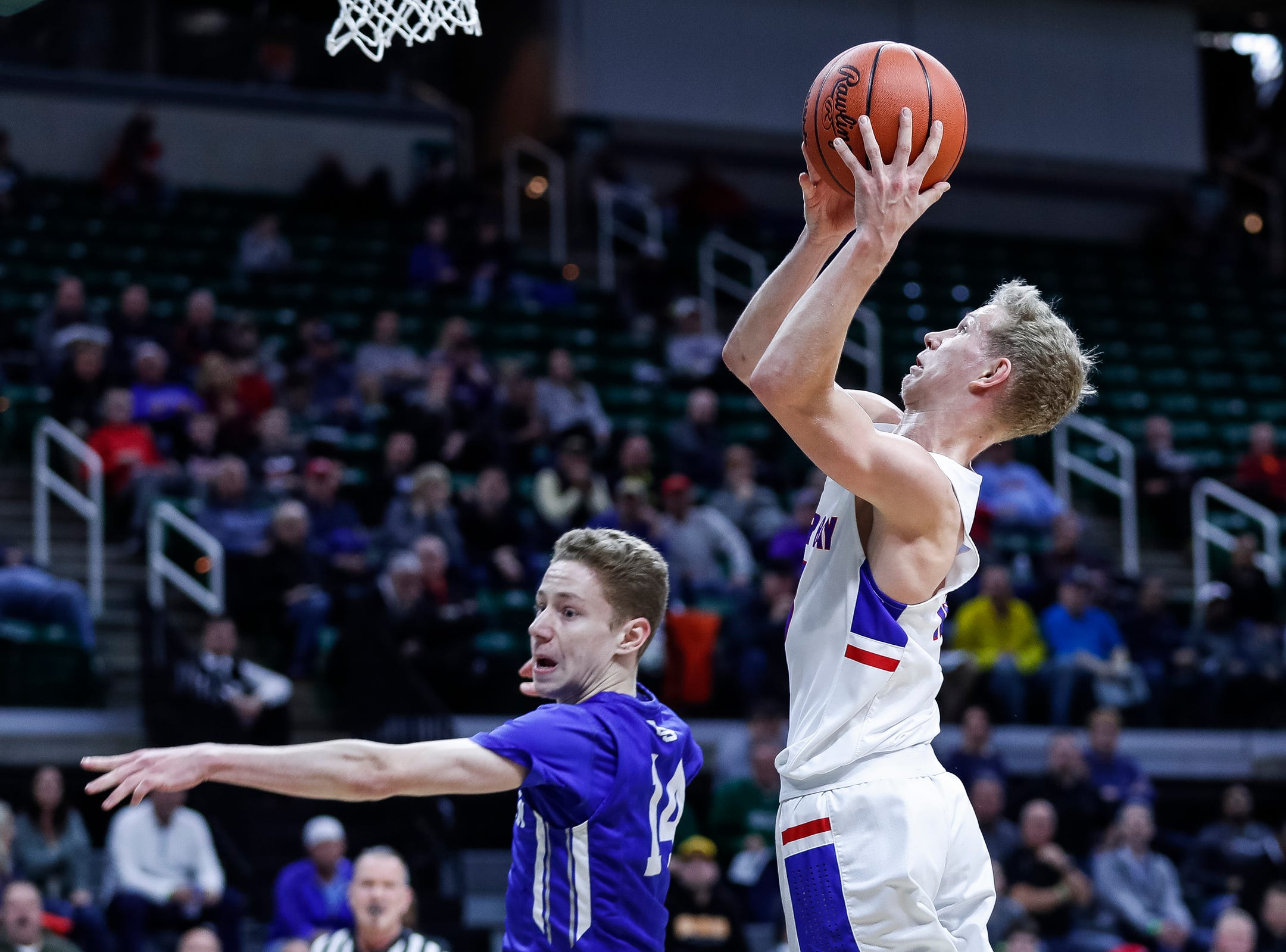 Dollar Bay Connor LeClaire (13) makes a layup against Southfield Christian's Noah Rheker (14) during the first half of MHSAA Division 4 semifinal at the Breslin Center in East Lansing, Thursday, March 14, 2019.