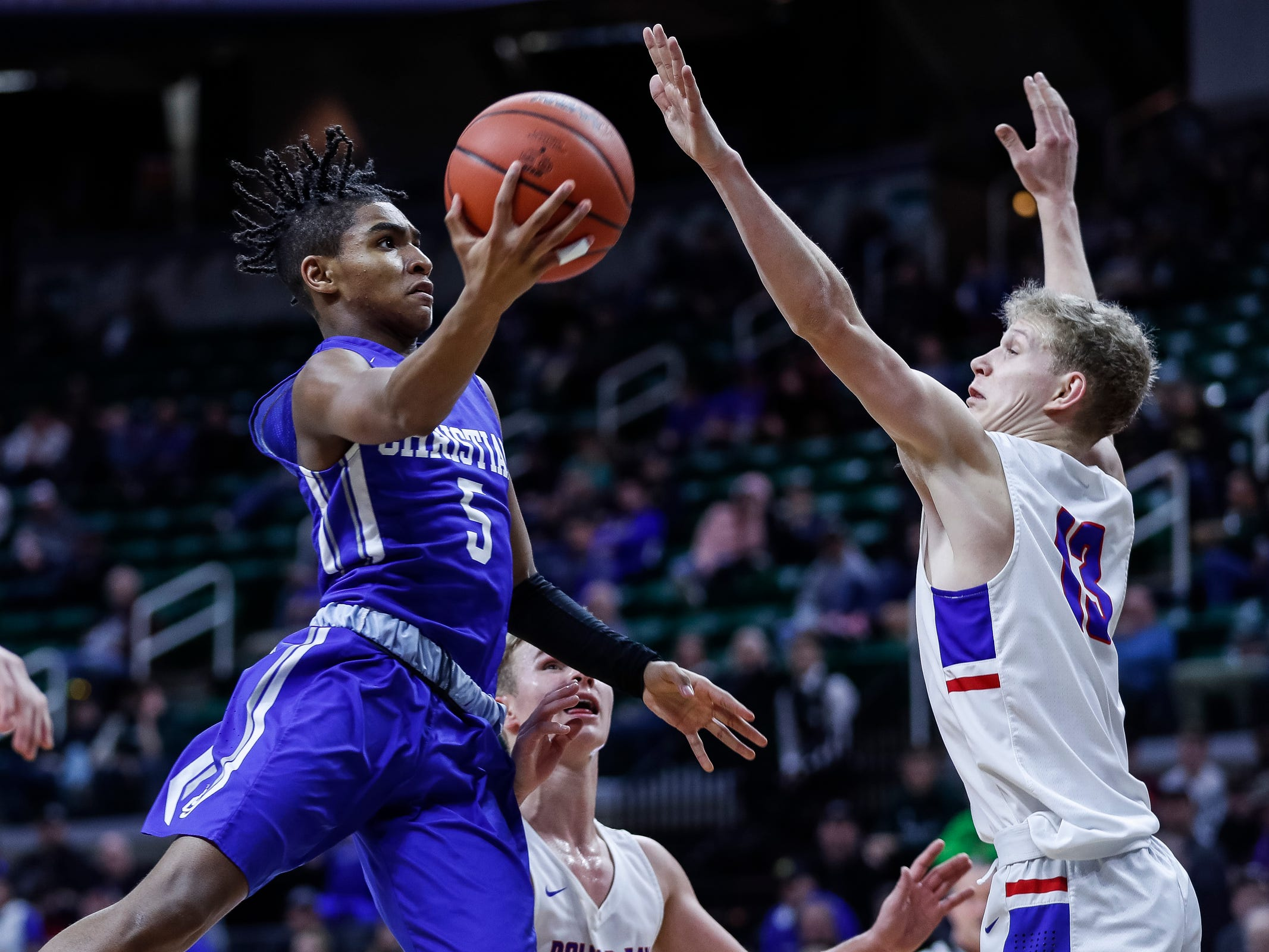 Southfield Christian's Verian Patrick (5) makes a layup against Dollar Bay's Connor LeClaire (13)during the second half of MHSAA Division 4 semifinal at the Breslin Center in East Lansing, Thursday, March 14, 2019.