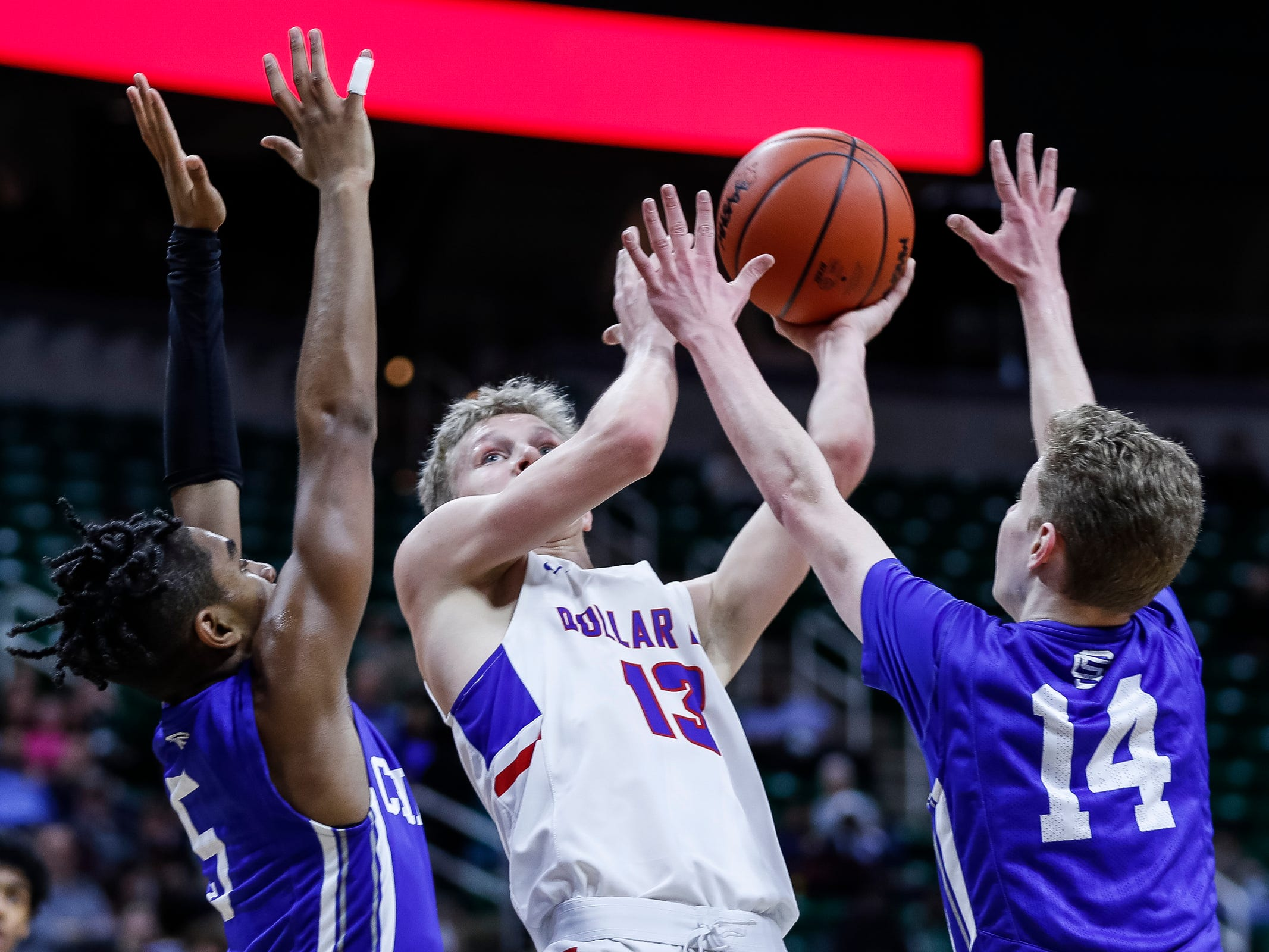Dollar Bay's Connor LeClaire (13) makes a layup against Southfield Christian Verian Patrick (5) and Noah Rheker (14) during the second half of MHSAA Division 4 semifinal at the Breslin Center in East Lansing, Thursday, March 14, 2019.