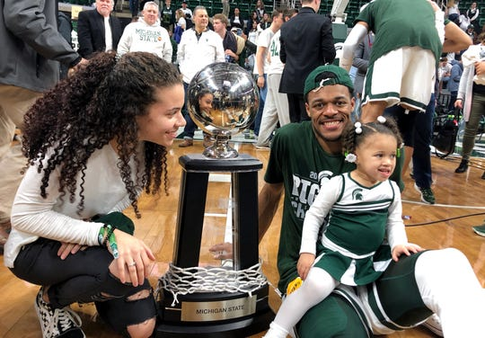 Michigan State basketball player Xavier Tillman smiles at the camera as he sits with his 2-year-old daughter Ayanna in his lap and his fiancee Tamia Todd looking on after MSU beat Michigan and earned a share of the Big Ten championship with Purdue on Sunday, March 10, 2019.