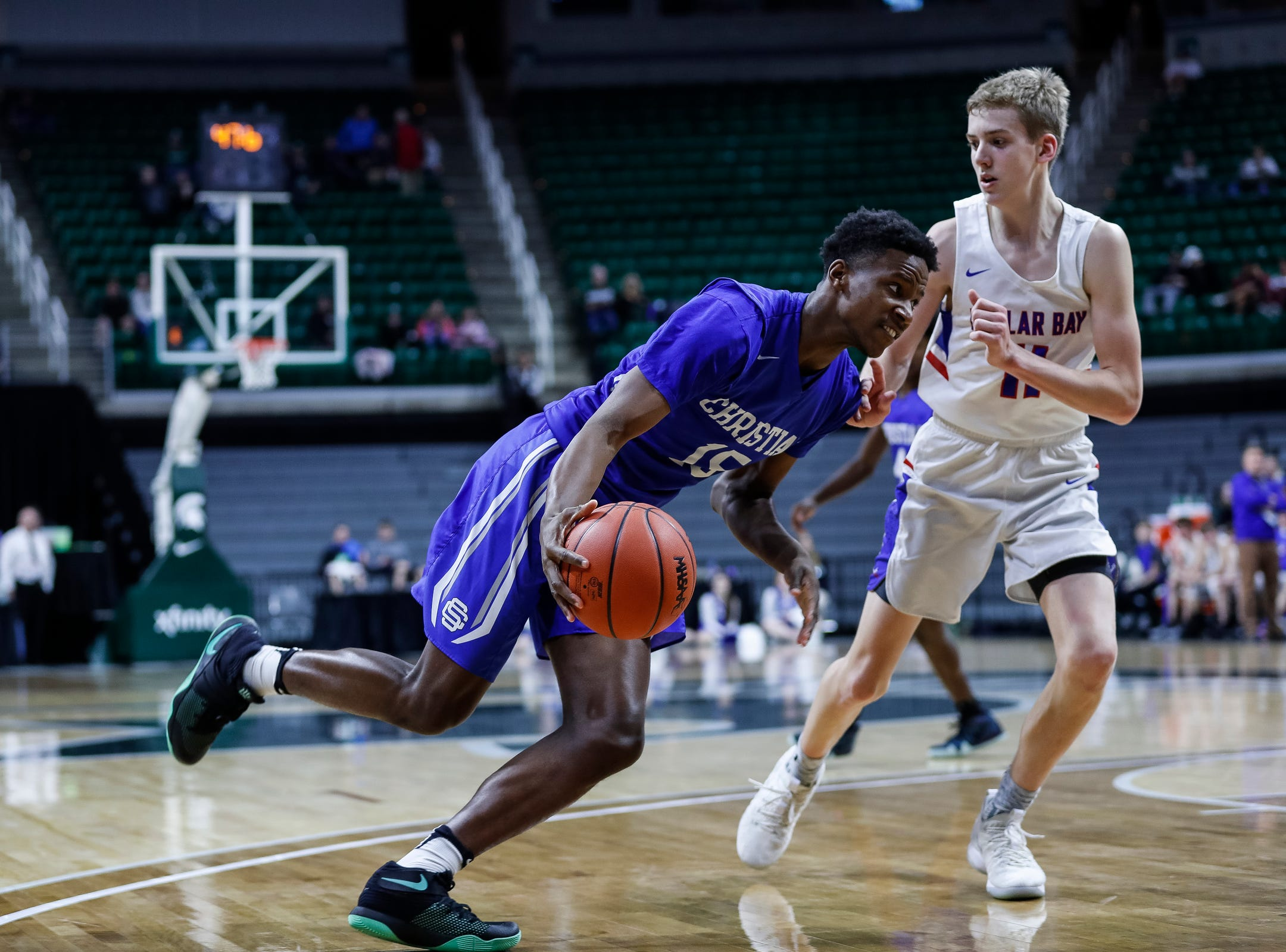 Southfield Christian's Greg Hines (15) dribbles against Dollar Bay's Ashton Janke (11) during the second half of MHSAA Division 4 semifinal at the Breslin Center in East Lansing, Thursday, March 14, 2019.