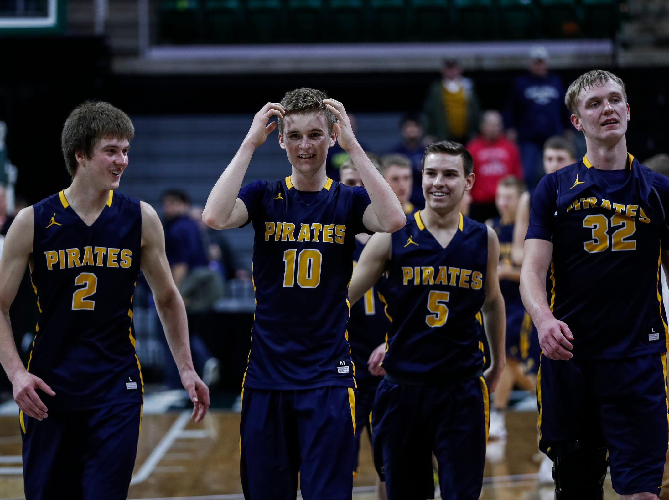 Pewamo-Westphalia players Nathan Wirth (2), Hunter Hengaesbach (10), Evyn Moffitt (5), and Andre Smith (32) celebrate their victory against Erie-Mason at the MHSAA Division 3 semifinal at the Breslin Center in East Lansing, Thursday, March 14, 2019.