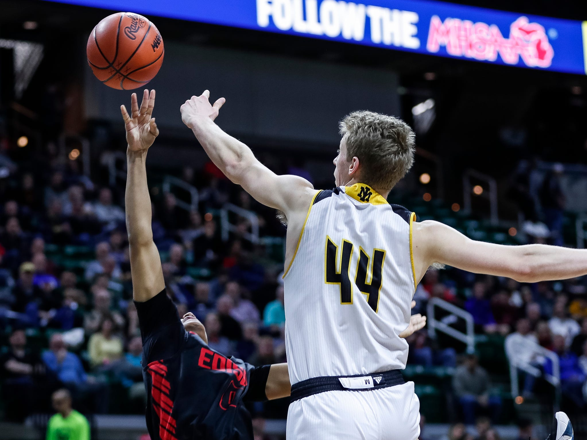 Iron Mountain's Charlie Gerhard blocks a shot from Detroit Edison's Ralph Bland during the first half of MHSAA Division 3 semifinal at the Breslin Center in East Lansing, Thursday, March 14, 2019.