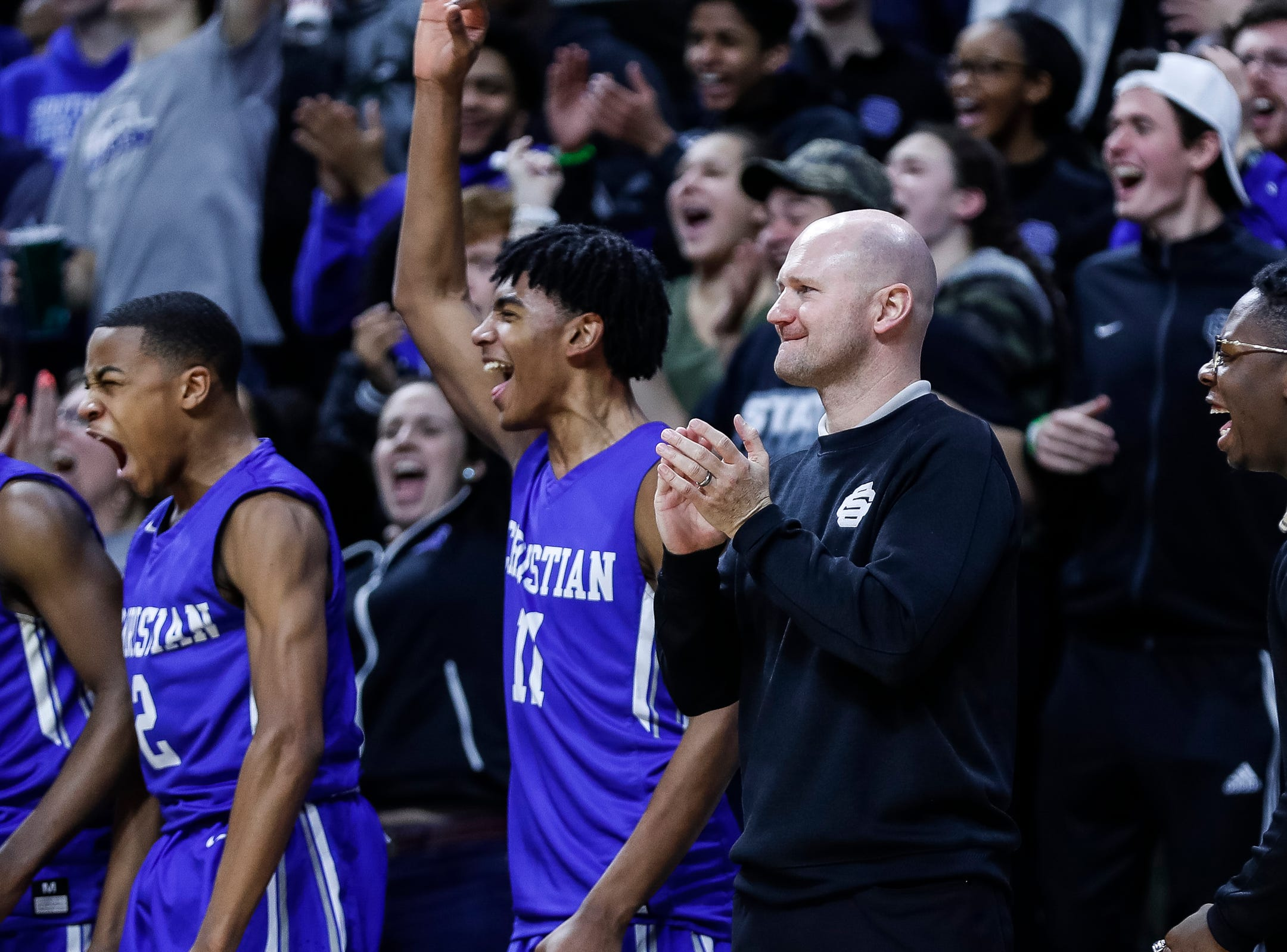 Southfield Christian head coach Josh Baker and the bench cheer for their teammates during the second half of MHSAA Division 4 semifinal against Dollar Bay at the Breslin Center in East Lansing, Thursday, March 14, 2019.