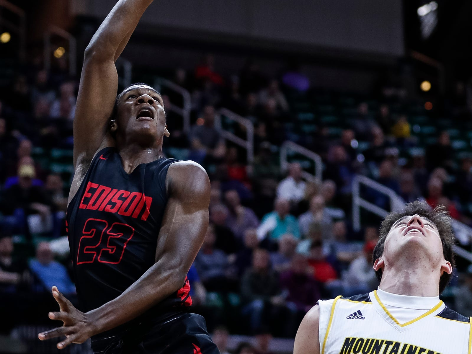Detroit Edison's Raynard Williams makes a layup against Iron Mountain's Jaden Vicenzi during the first half of MHSAA Division 3 semifinal at the Breslin Center in East Lansing, Thursday, March 14, 2019.