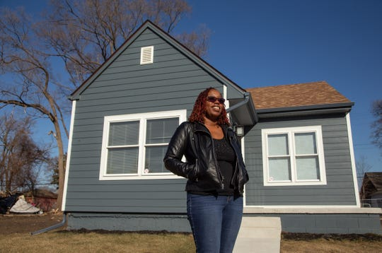 Jomica Miller stands in front of her house she recently purchased on Detroit's northwest side on Tuesday, March 12, 2019.