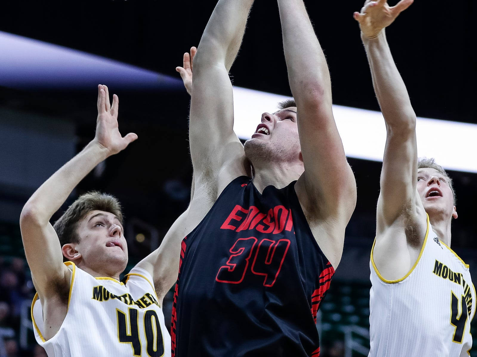 Detroit Edison's Bryce George (34) battles for a rebound with Iron Mountain's Tony Feira (40) during the first half of MHSAA Division 3 semifinal at the Breslin Center in East Lansing, Thursday, March 14, 2019.