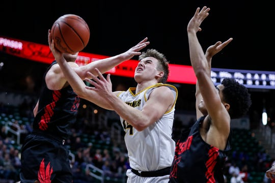 Iron Mountain's Marcus Johnson (14) makes a layup against Detroit Edison during the second half of the MHSAA Division 3 semifinal at Breslin Center in East Lansing, Thursday, March 14, 2019.