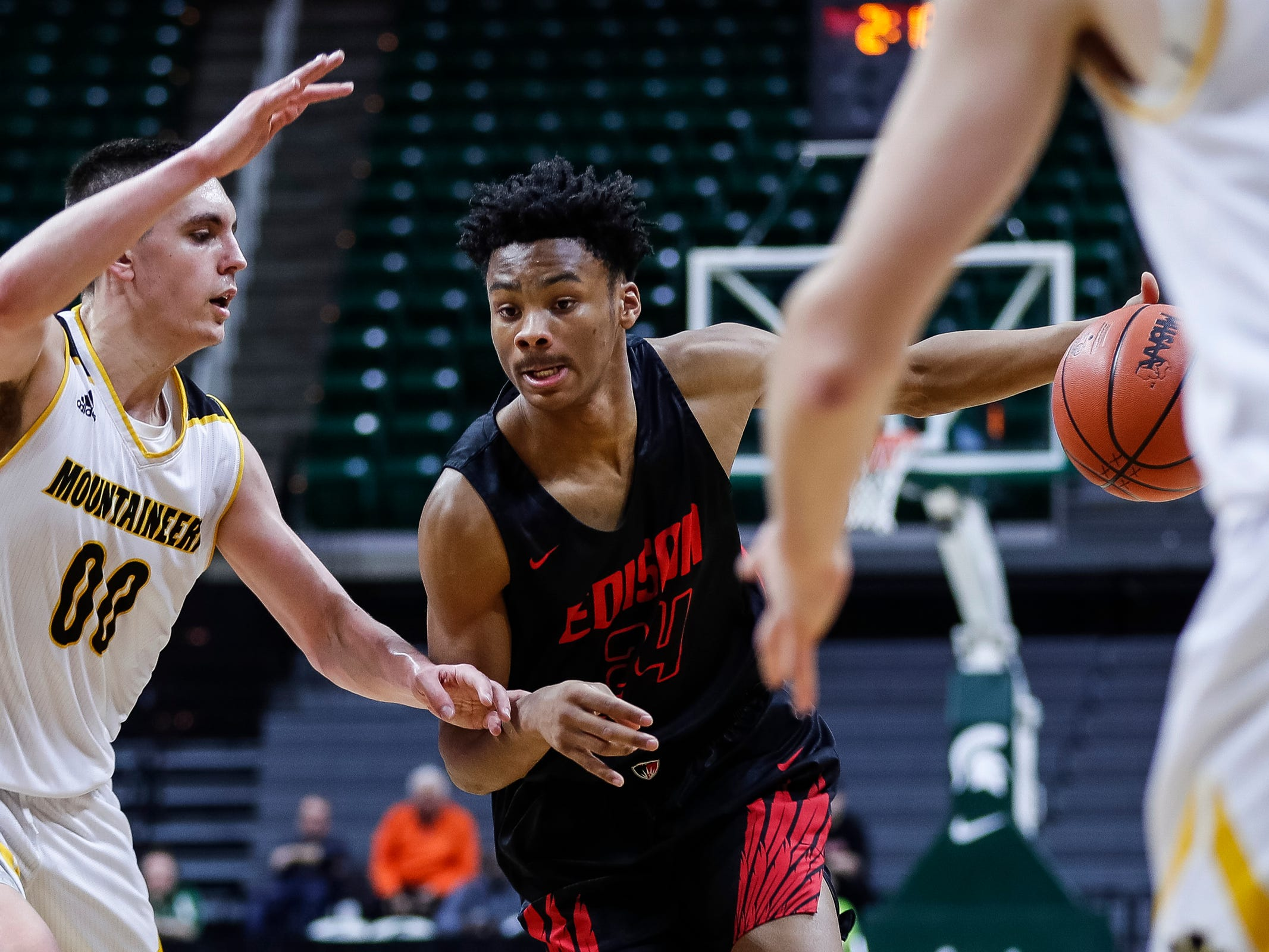 Detroit Edison's Dylan Bell dribbles against Iron Mountain's Foster Wonders during the first half of MHSAA Division 3 semifinal at the Breslin Center in East Lansing, Thursday, March 14, 2019.