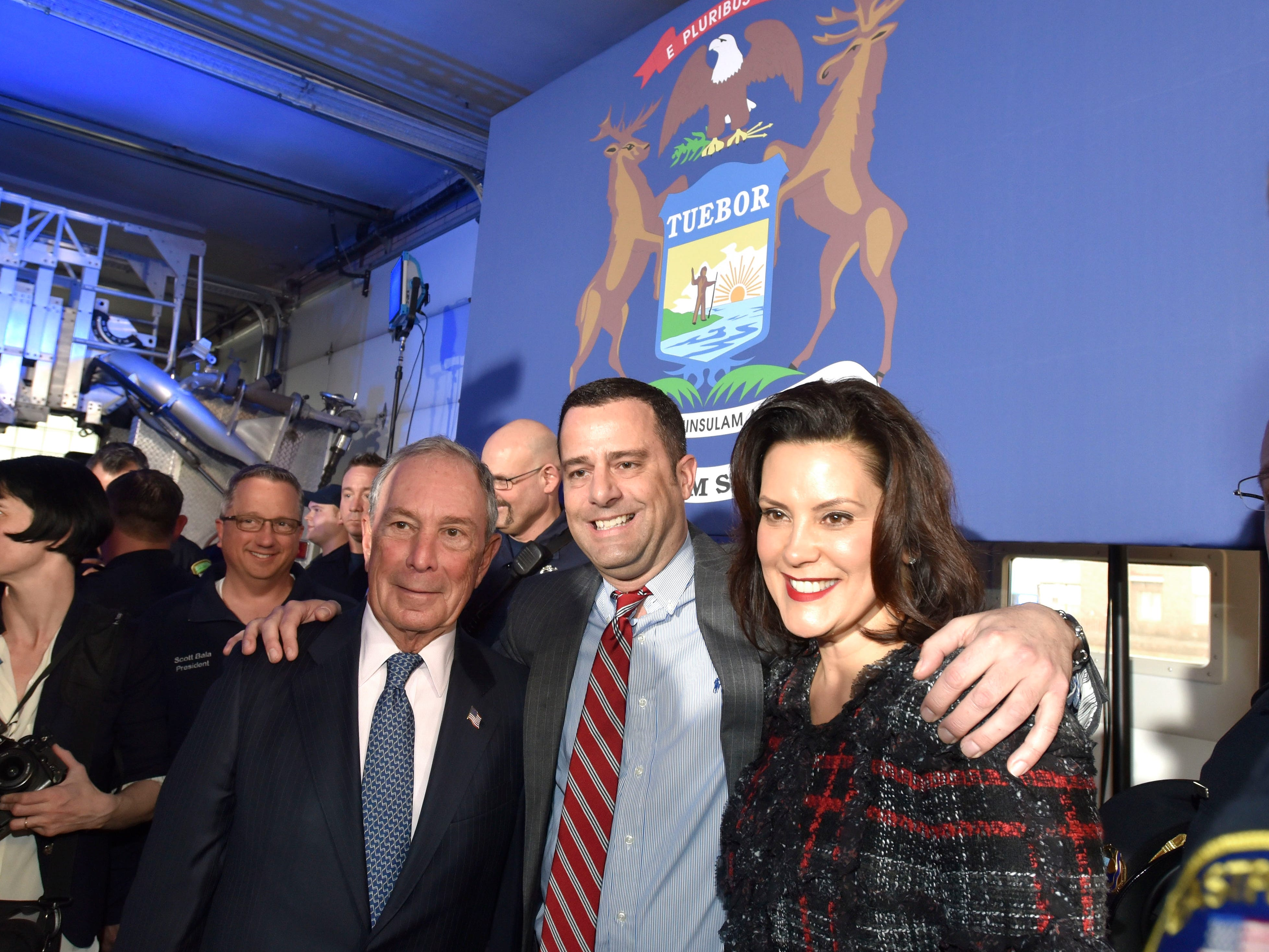 Former City of New York Mayor Michael Bloomberg, left, and Michigan Governor Gretchen Whitmer, right, take pictures with attendees after the press conference.