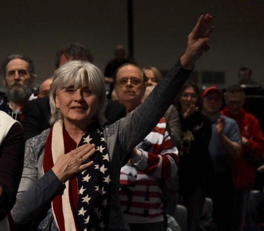 "Beverly Marshall of St. Clair Shores pays tribute during the national anthem. Supporters gather to listen to speakers at a ""We Build The Wall"" town hall meeting at Cobo Center in Detroit on March 14, 2019."