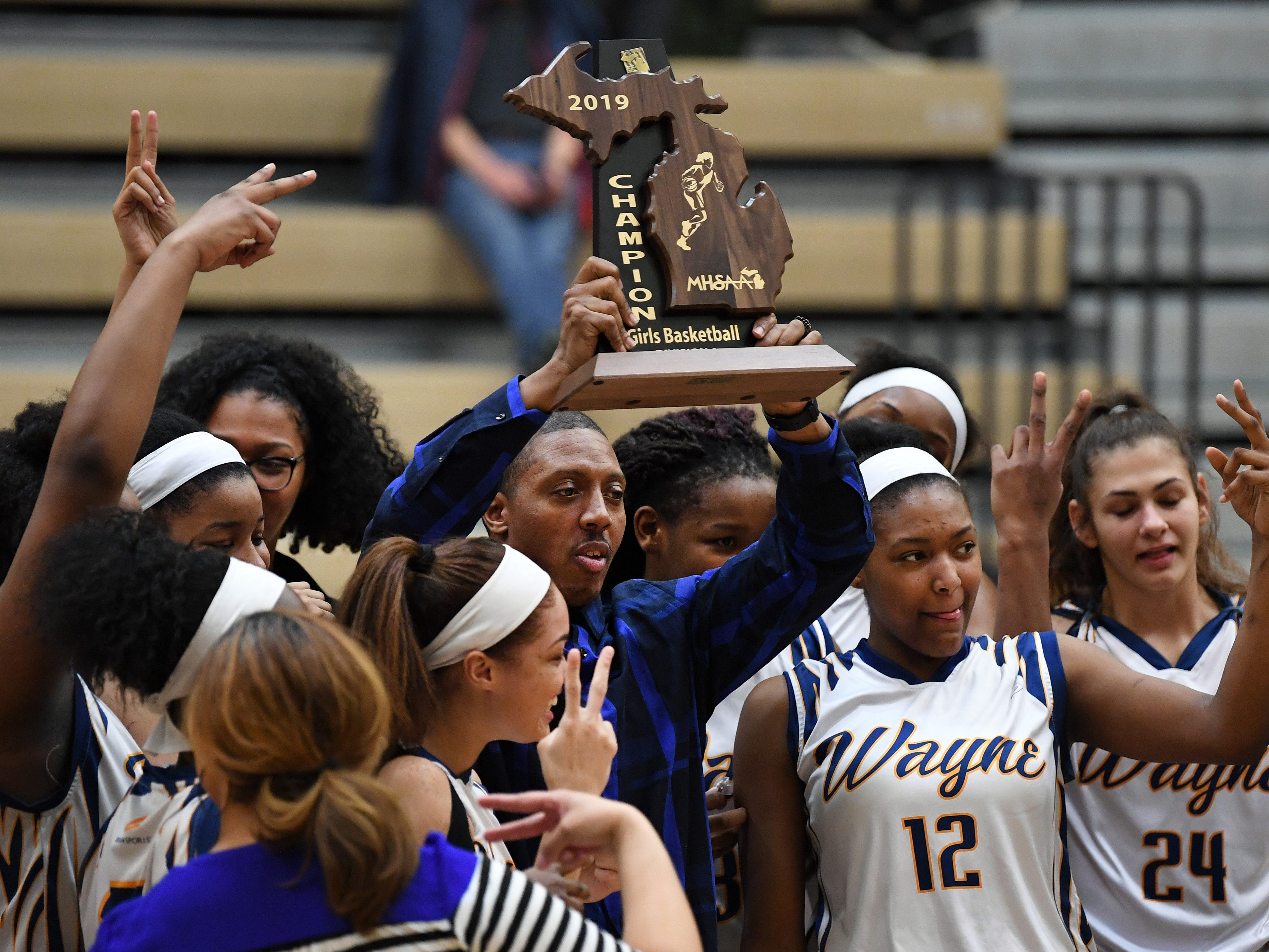 Wayne Memorial girls basketball head coach Jarvis Mitchell, center, is surrounded by his team as he hoists a Division 1 regional trophy following a 53-35 win over Ann Arbor Pioneer, Wednesday, March 13, 2019, at Skyline HS in Ann Arbor, Michigan.