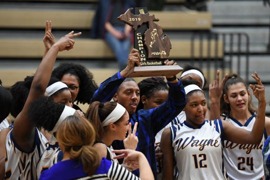Wayne Memorial girls basketball head coach Jarvis Mitchell, center, is surrounded by his team as he hoists a Division regional championship trophy following his team's win over Ann Arbor Pioneer.