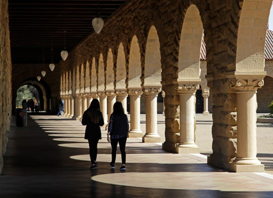 Students walk on the Stanford University campus Thursday, March 14, 2019, in Santa Clara, Calif.