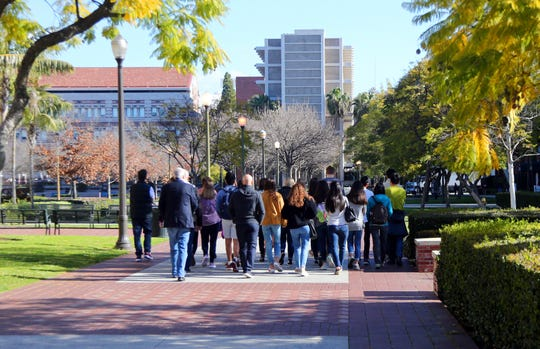 In this Tuesday, March 12, 2019 photo, prospective students and parents tour the campus of the University of Southern California in Los Angeles. U