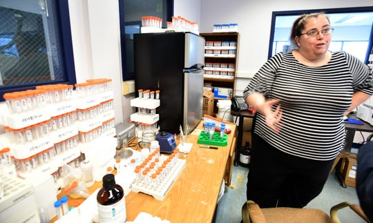Merit Labs in East Lansing does testing for PFAS chemical compounds for the state of Michigan. Merit's labs use Liquid Cromatography-Mass Spectrometry machines to search for the compounds. Samples and containers and markers crowd the work space in the foreground. (Dale G.Young/Detroit News) 2019.