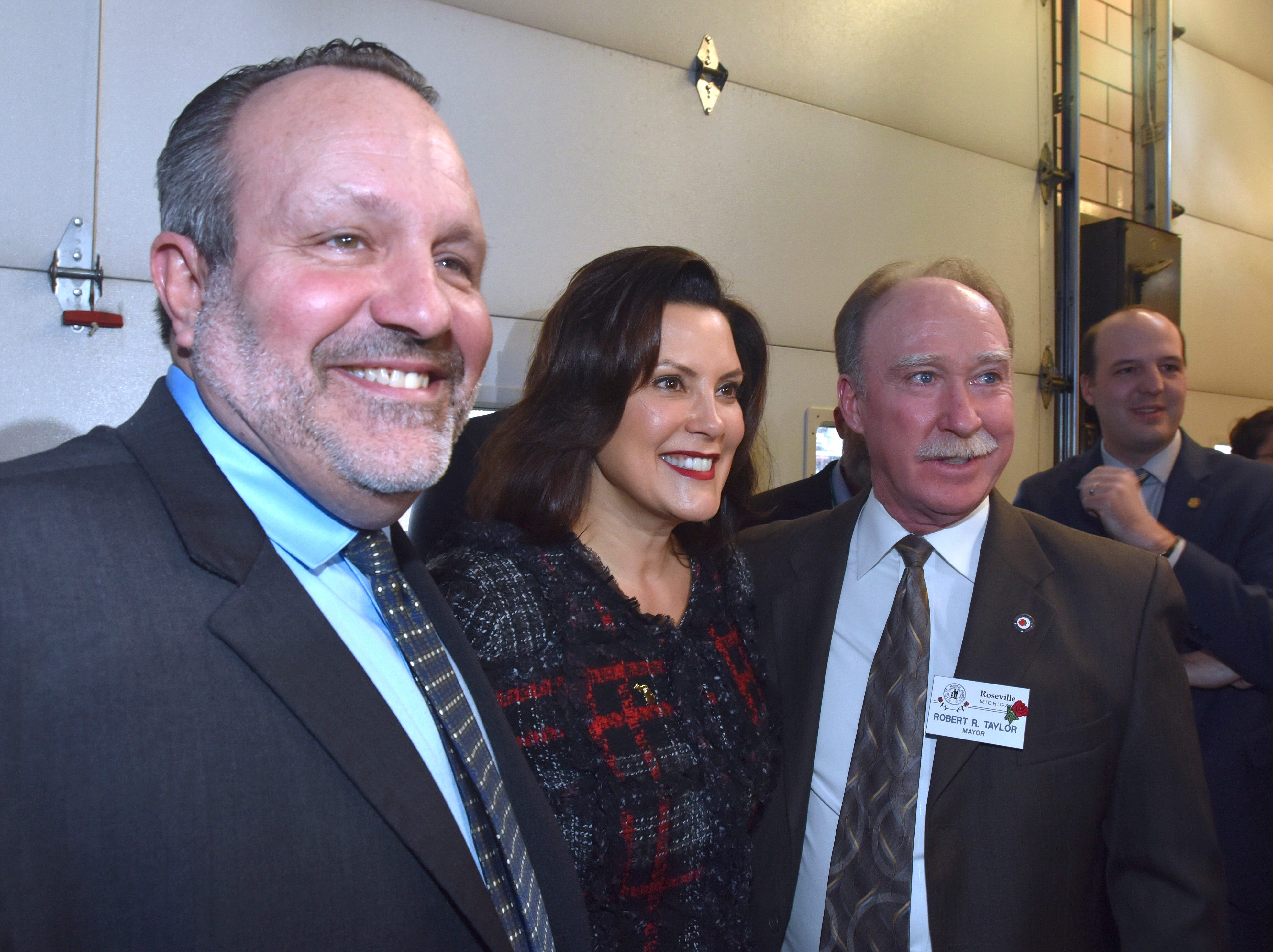 Center Line Mayor Robert Binson, left, and Roseville Mayor Robert Taylor, right, pose with Michigan Governor Gretchen Whitmer, center, after the press conference.