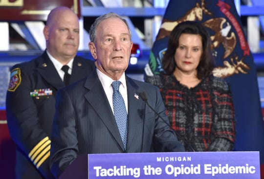 Former City of New York Mayor Michael Bloomberg speaks from the podium as Eastpointe Deputy Fire Chief Nick Sage, left, and Michigan Governor Gretchen Whitmer, right, listen.