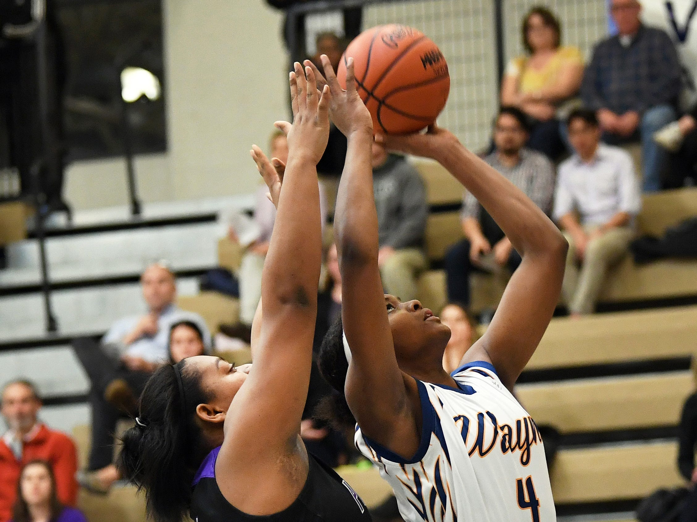 Wayne Memorial forward Alanna Micheaux puts up a shot as she is guarded by Ann Arbor Pioneer center Asaria Turman in the first quarter.