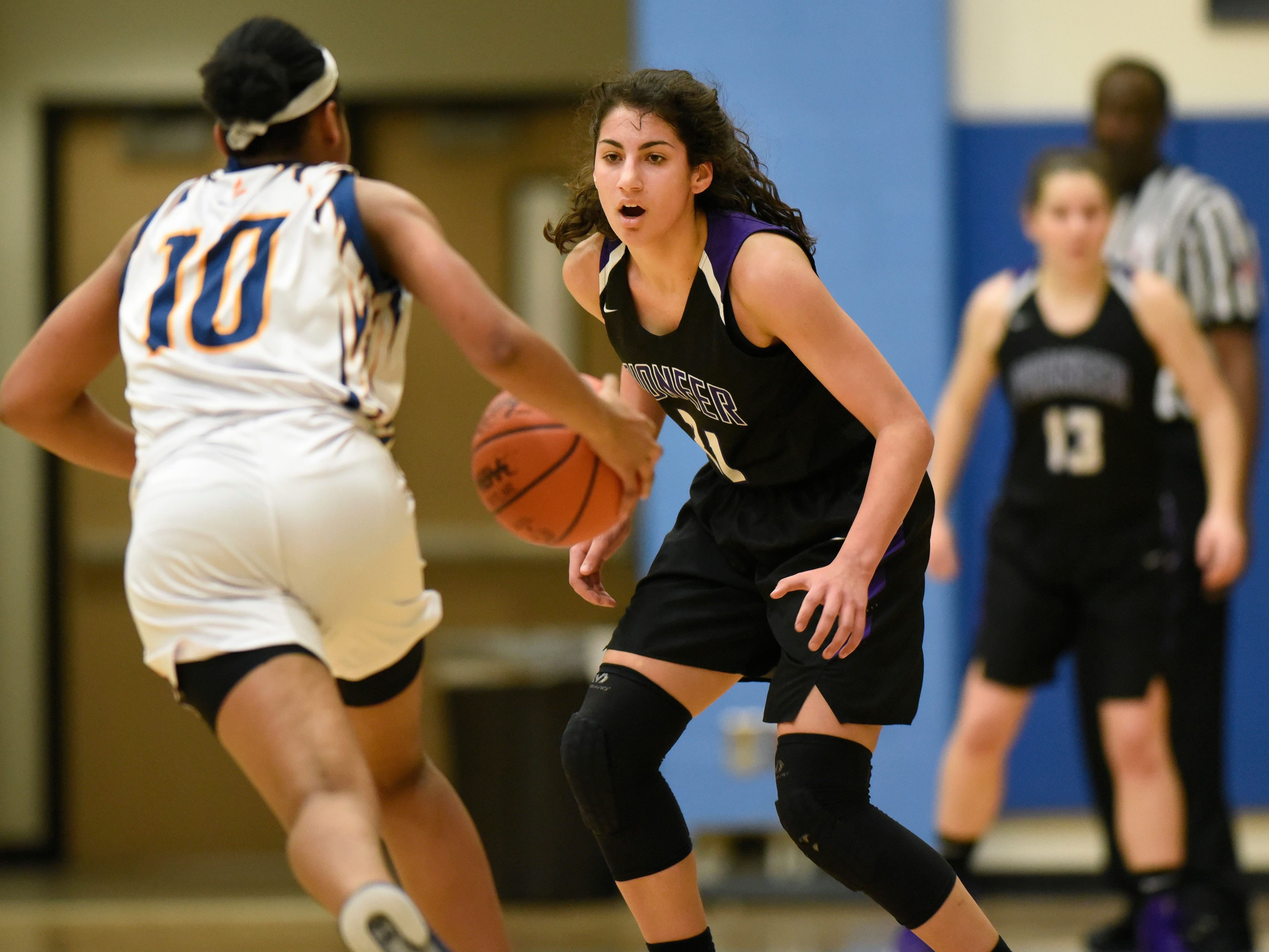 Wayne Memorial guard Jeanae Terry drives to the basket as she is guarded by Ann Arbor Pioneer forward Corine Burgard in the first quarter.