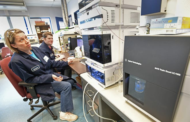Jessica Hart and Chad McAlvey work at Merit Labs in East Lansing, using the Liquid Cromatography-Mass Spectrometry machine in the foreground to search for the compounds.