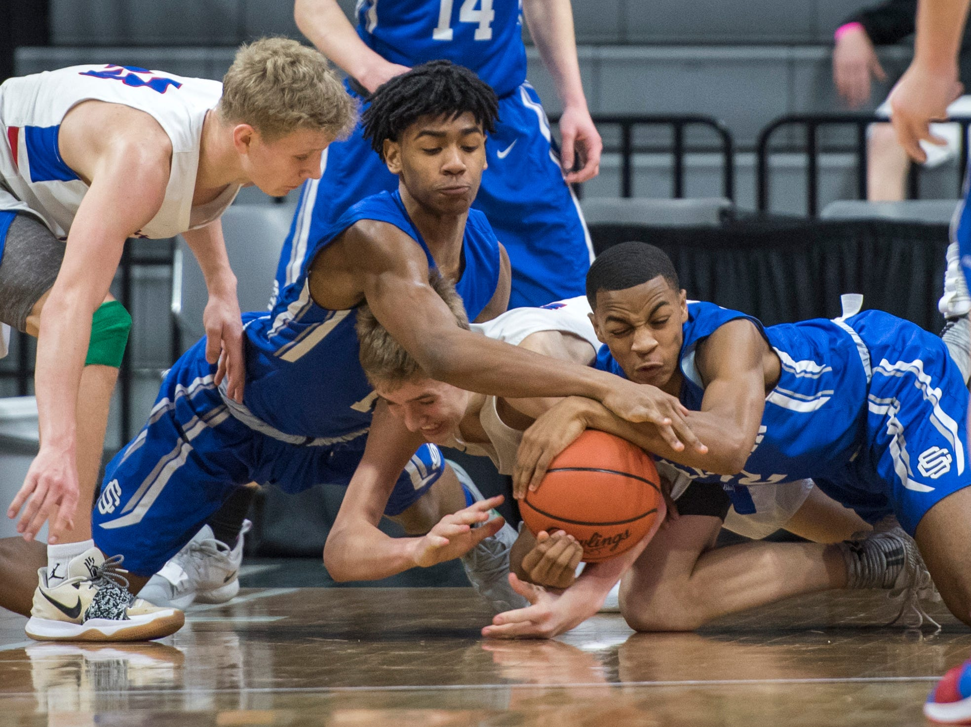 Southfield Christian's Malcolm King, Dollar Bay's Ashton Janke and Southfield Christian's Ronald Johnson fight for possession of the ball in the second half of the 52-28 Southfield victory in the Division 4 semifinals.