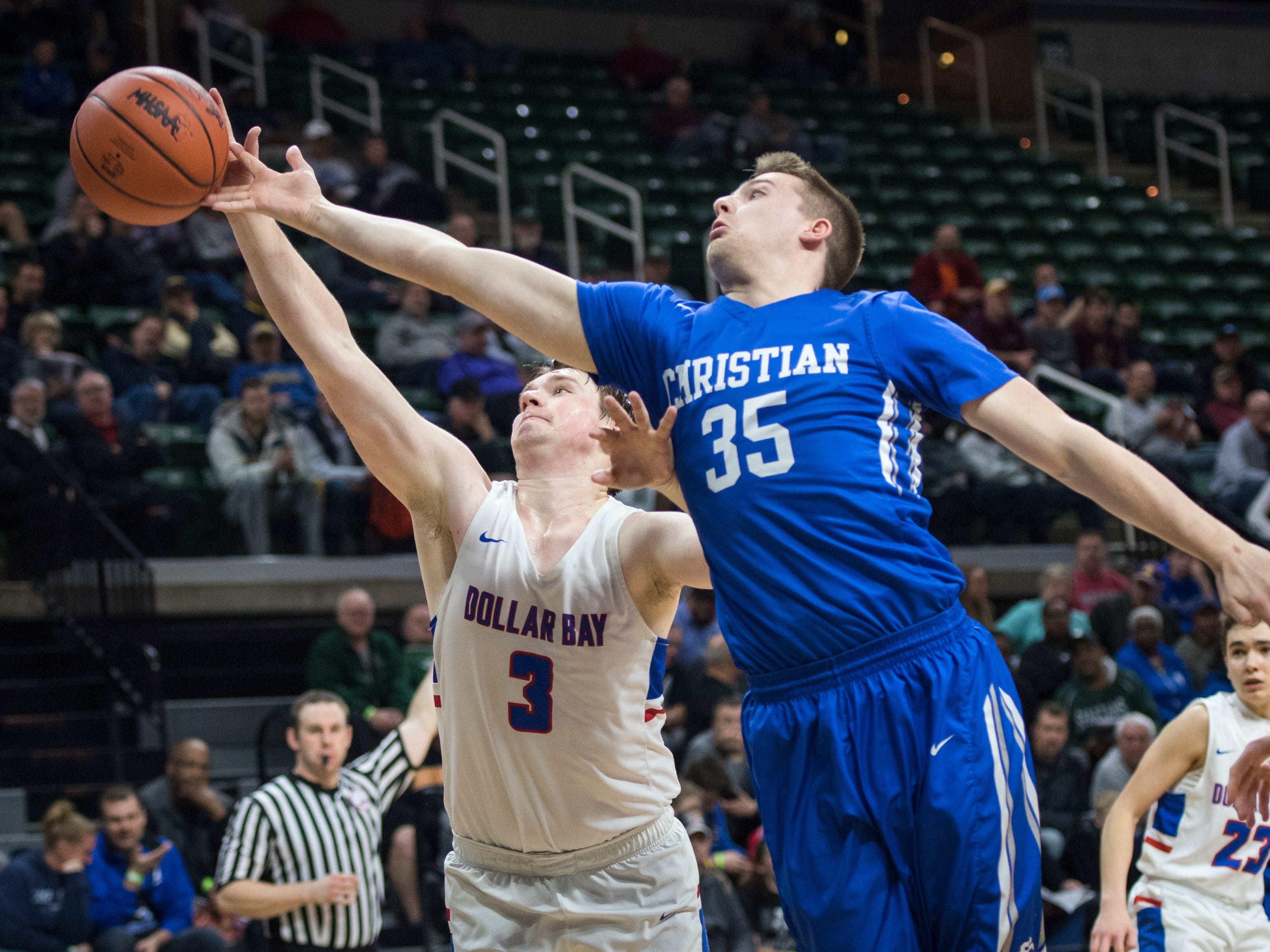 Dollar Bay's Drake Schmitz and Southfield Christian's Will Harahan reach for a loose ball in the second half. '