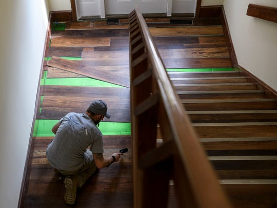 Kyle Houghland of Bellomy Interiors puts down flooring in  one of the many hallways of the historic Rathbone building located near Haynie's Corner in Evansville, Ind., Wednesday, March 13, 2019.