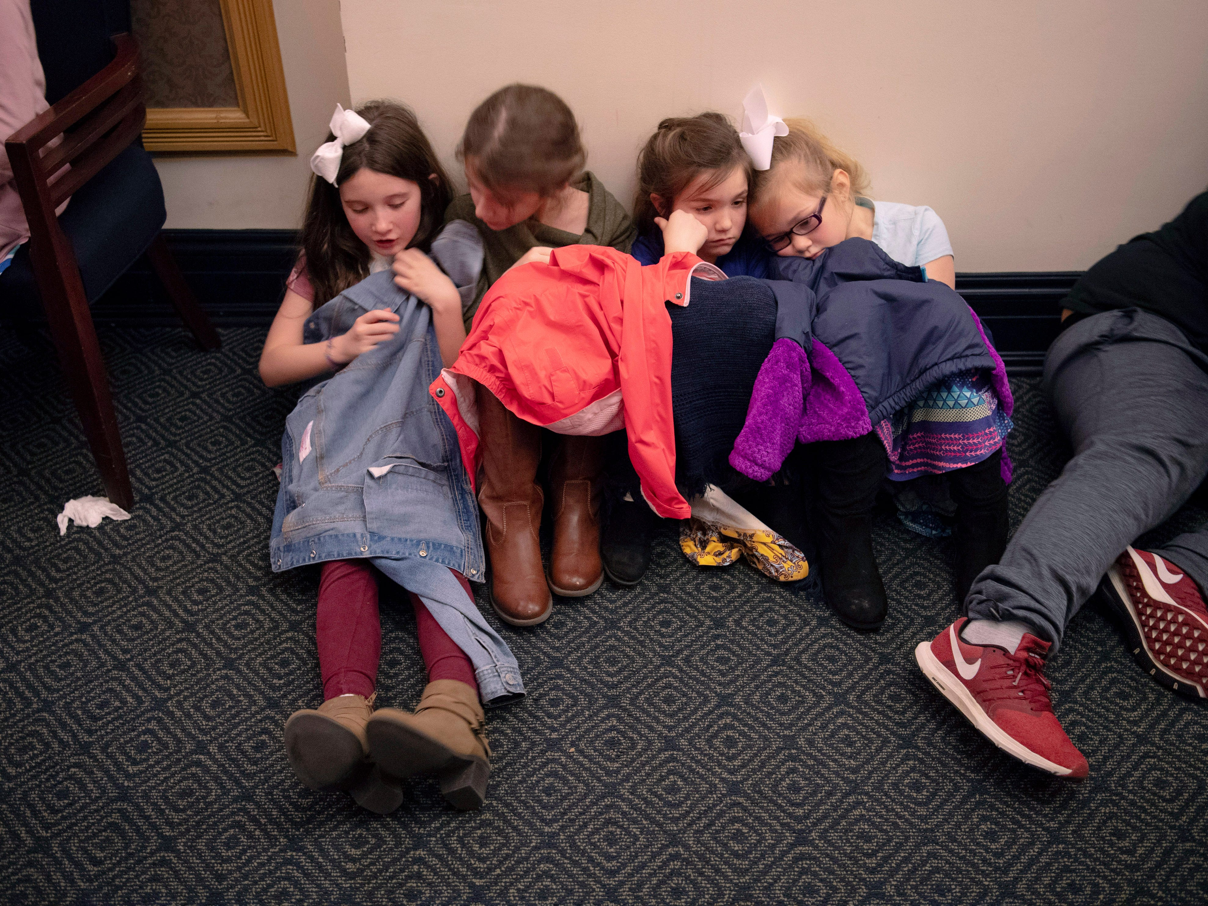 Cynthia Heights Elementary School students, from left, Ashlynn Blanchard, 9, Amelia Brendel, 9, Emma Tenbarge, 8, and Kaleigh Volk, 8, wait out the tornado warnings from the hallway of The Victory Thursday morning. Evansville Philharmonic Orchestra made it through the first of their Young People's Concerts before a series of tornado warnings forced them to take shelter.