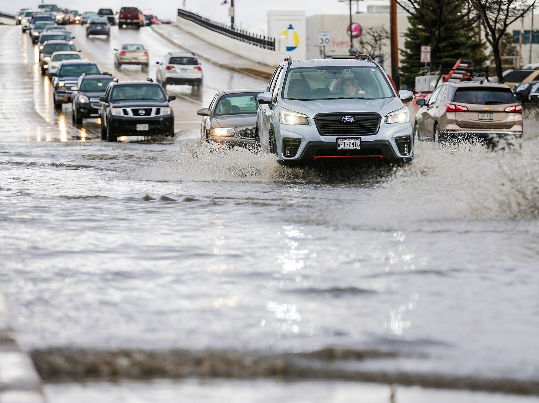 Cars travel through high water Thursday, March 14, 2019 on west Johnson Street in Fond du Lac, Wisconsin. Ice jams on the east branch of the Fond du Lac River and heavy rainfall caused flooding problems throughout the city.