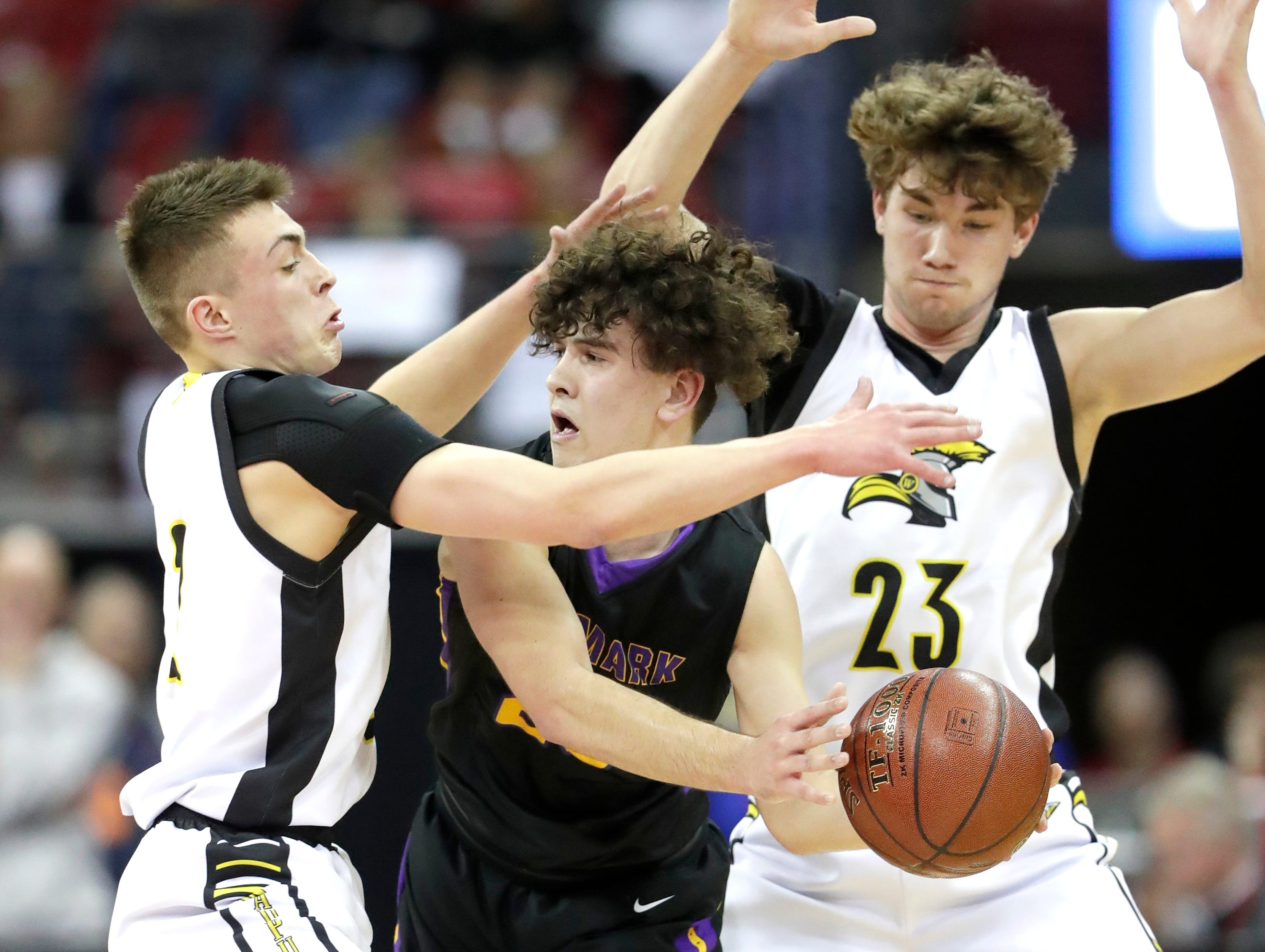Denmark High Schoo's #23 Brady Jensl against Waupun High School's #2 Trevor VandeZande, left, and  #23 Reece Homan, right, during their WIAA Division 3 boys basketball state semifinal on Thursday, March 14, 2019, at the KohlCenter in Madison, Wis.