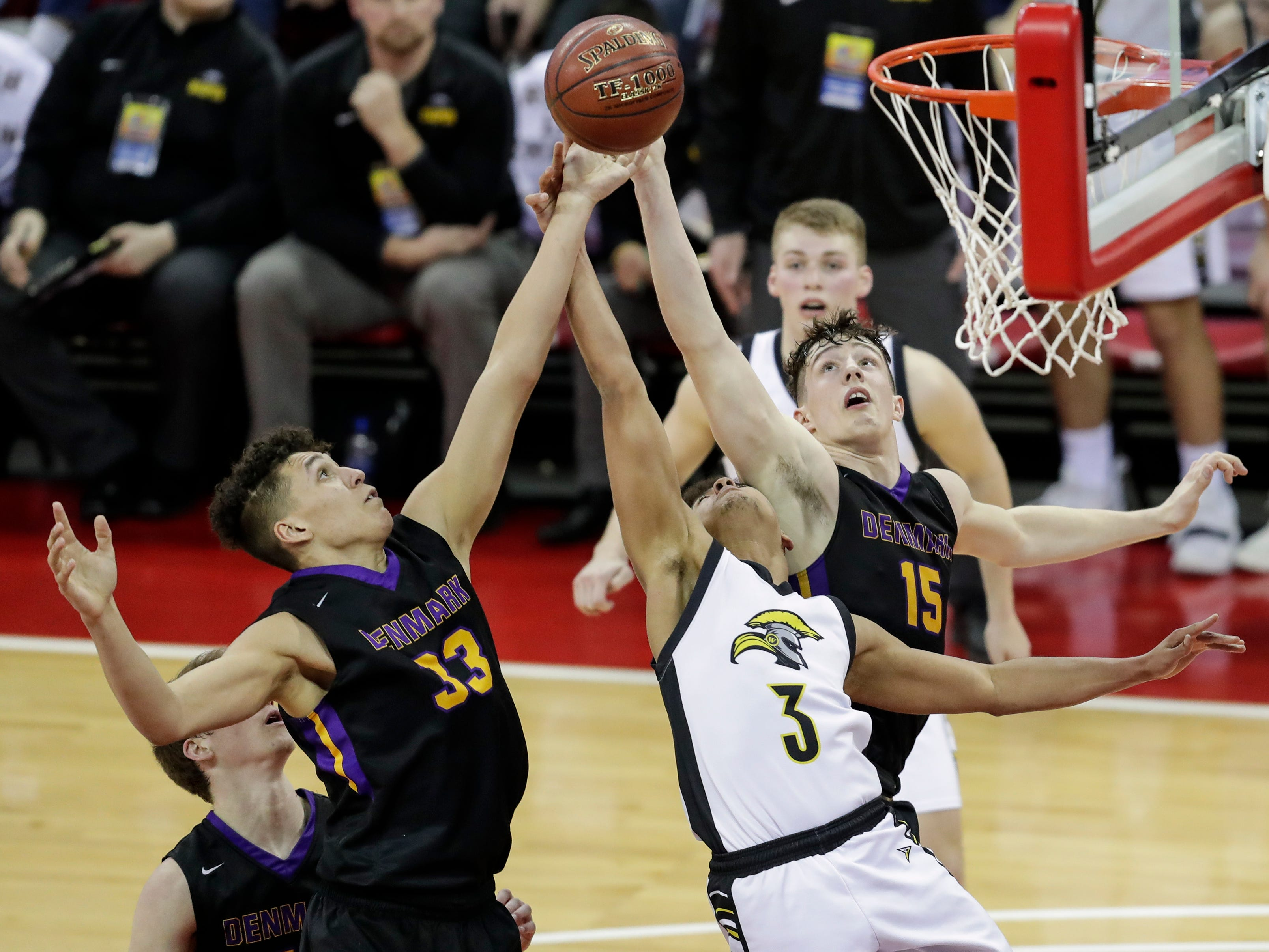 Denmark's Patrick Suemnick (33) and Zane Short (15) battle Waupun's Quintin Winterfeldt (3) for a rebound during their WIAA Division 3 boys basketball state semifinal at the Kohl Center Thursday, March 14, 2019, in Madison, Wis.