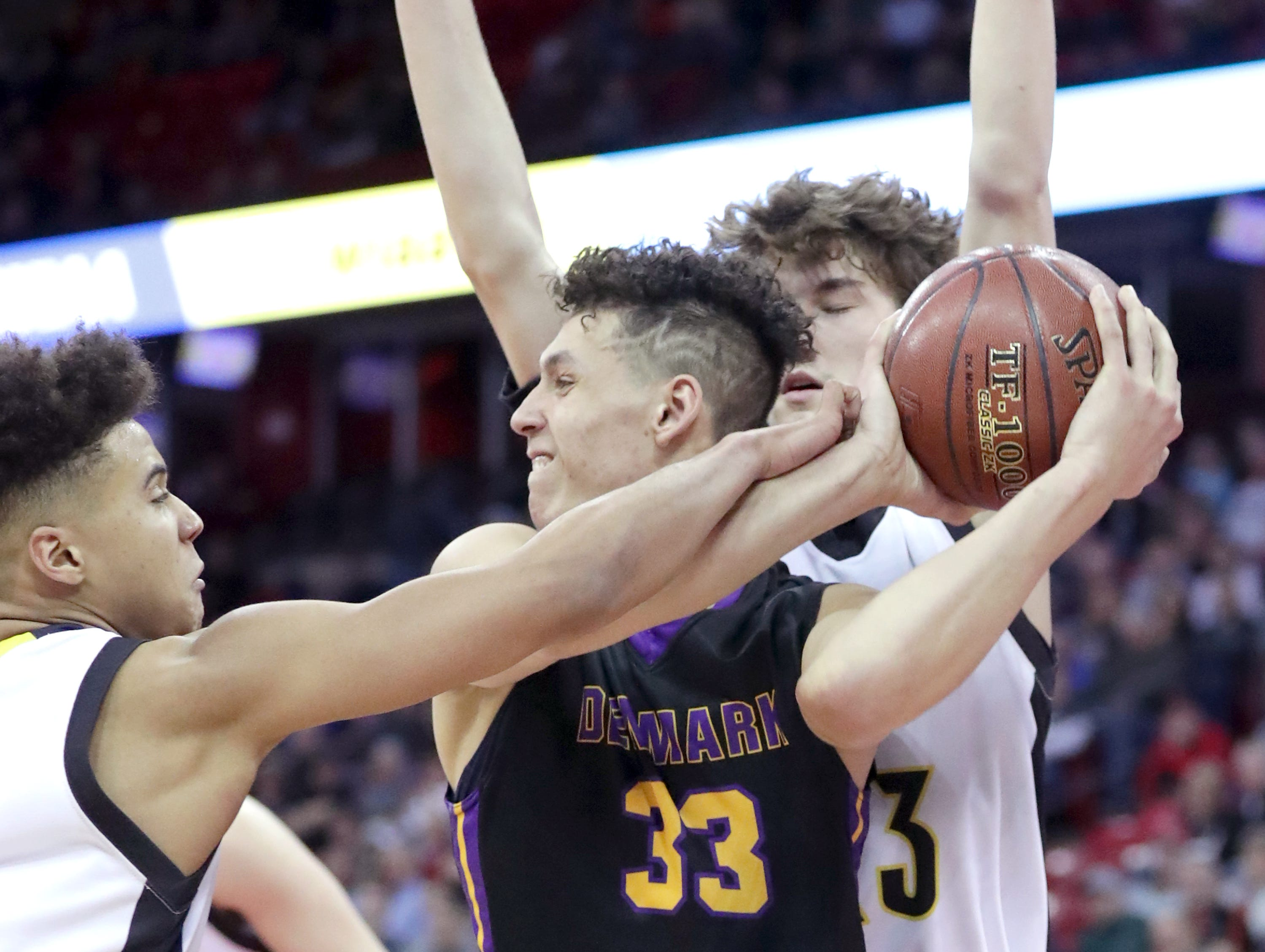 Denmark High School's #33 Patrick Suemnick against Waupun High School's #3 Quintin Winterfeldt, left, and #23 Reece Homan during their WIAA Division 3 boys basketball state semifinal on Thursday, March 14, 2019, at the KohlCenter in Madison, Wis.  Waupun defeated Denmark 60 to 43.