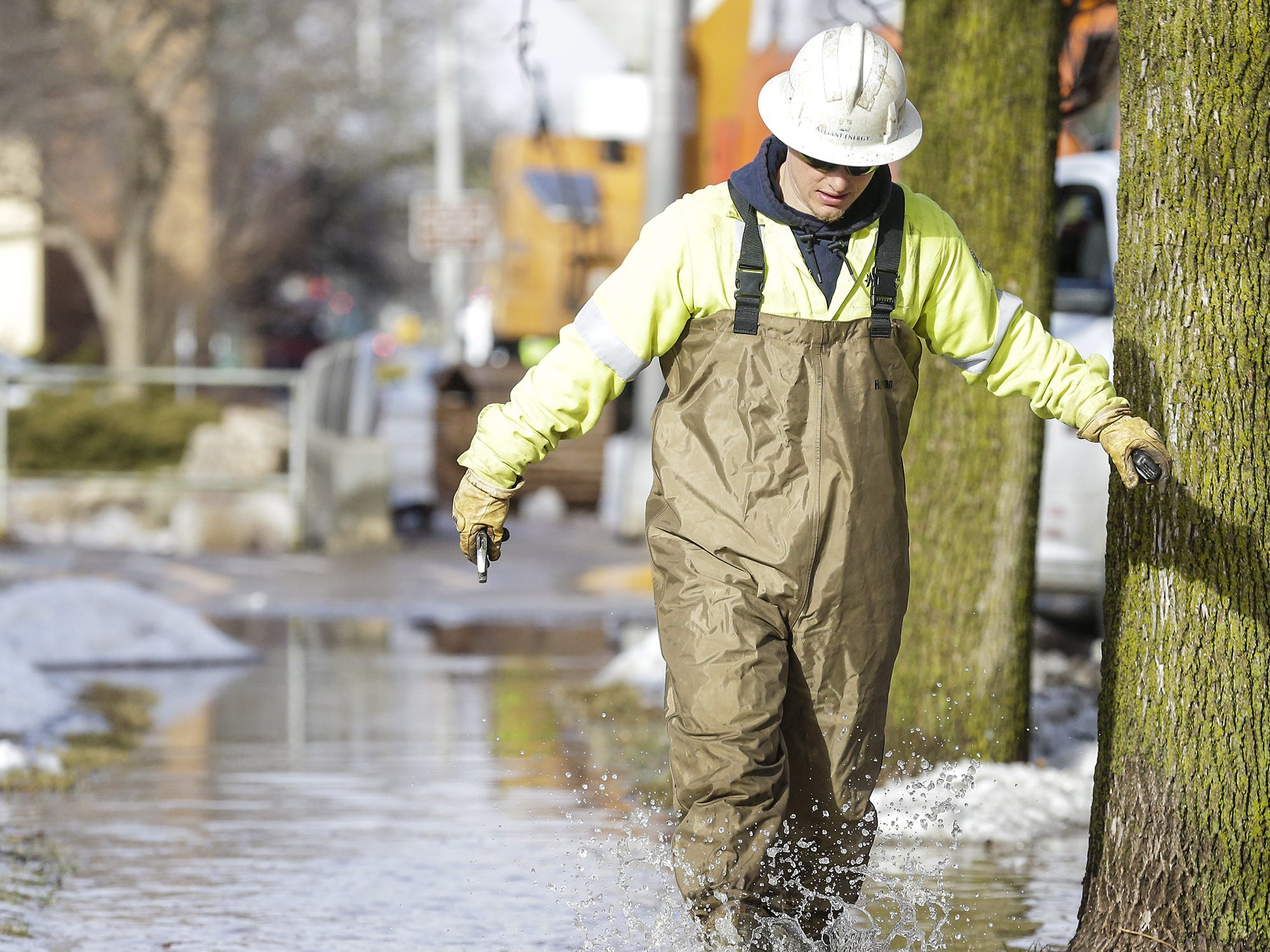 An Alliant Energy worker walks along a flooded sidewalk Thursday, March 14, 2019 on Western Avenue in Fond du Lac, Wis. Ice jams on the east branch of the Fond du Lac River caused localized flooding problems in the city. Doug Raflik/USA TODAY NETWORK-Wisconsin